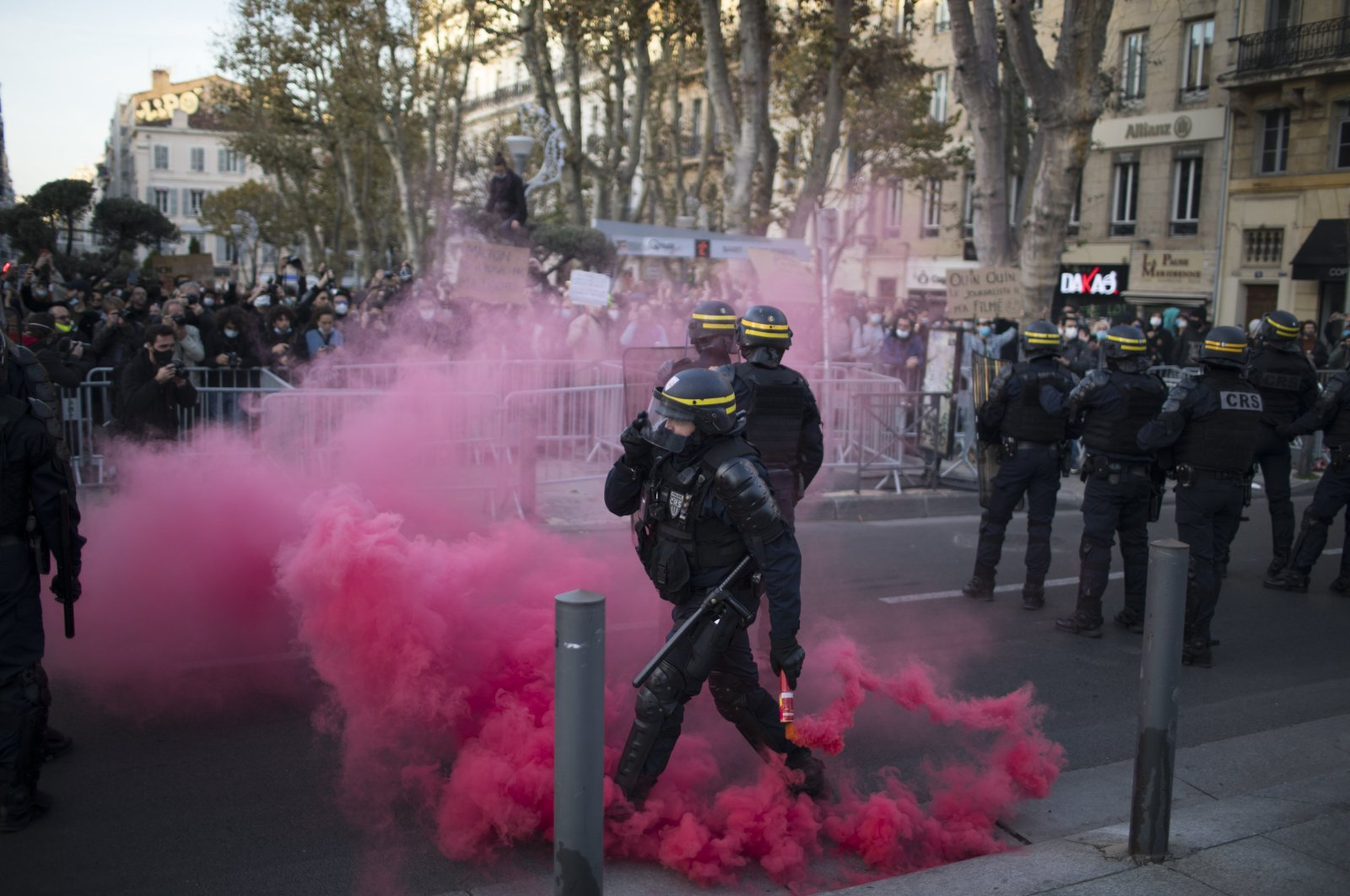 A French riot police officer clears a smoke flare thrown by protesters during a demonstration in Marseille, southern France, Nov. 21, 2020. (AP Photo)