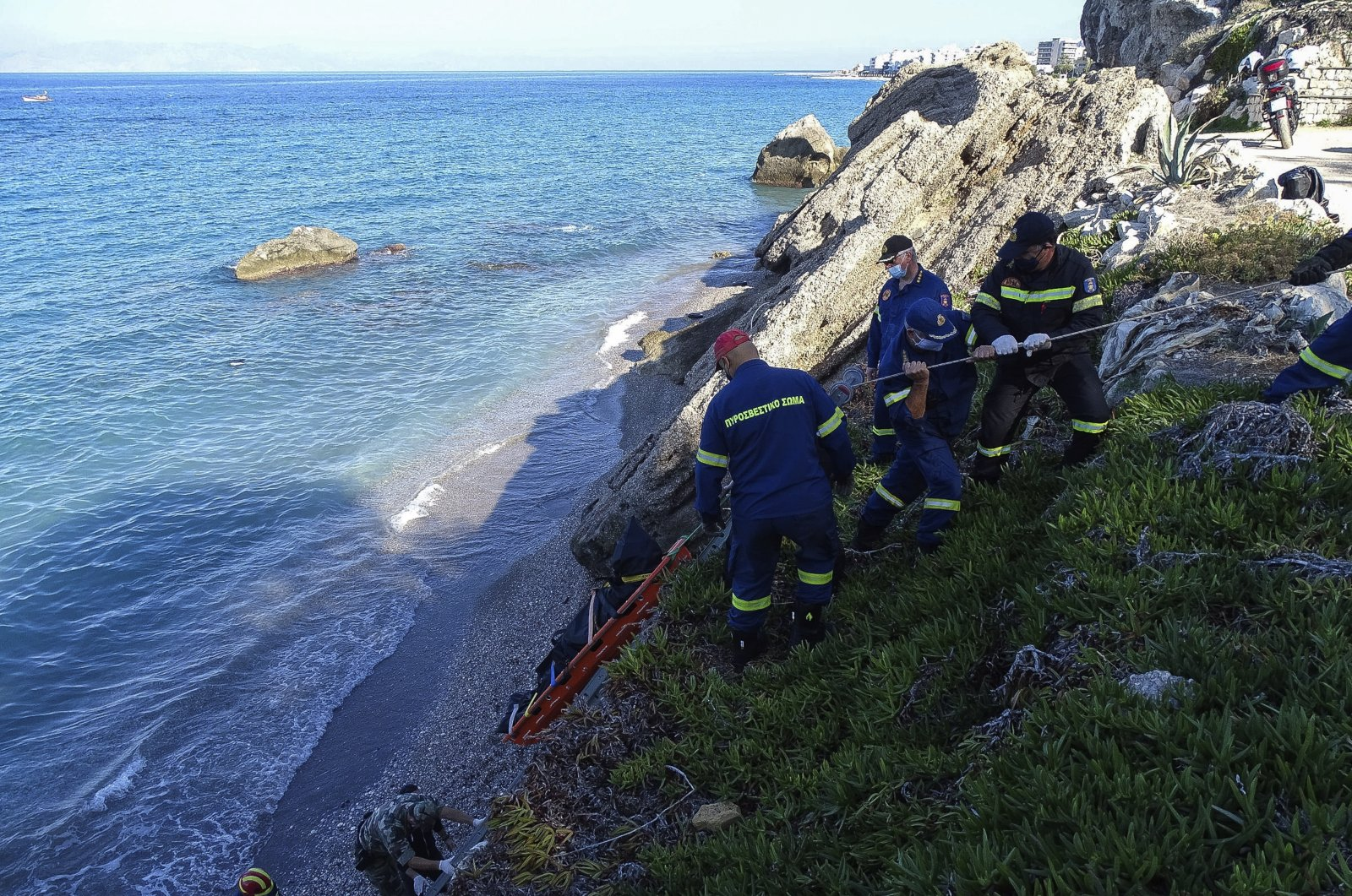 Firefighters retrieve the body of a migrant from the beach after a shipwreck on the island of Rhodes, southeastern Greece, Nov. 23, 2020. (AP Photo)