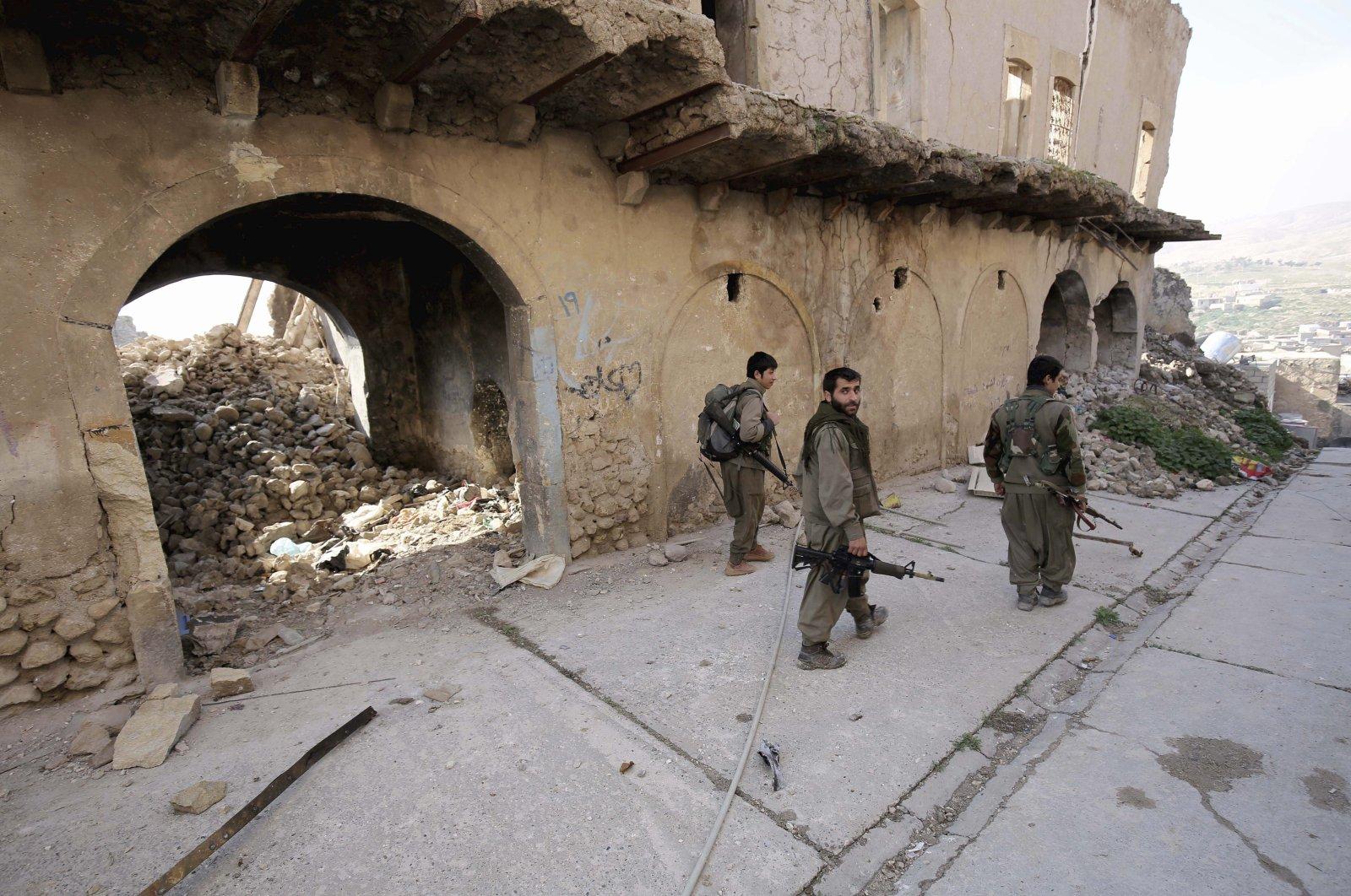 PKK terrorists walk in the damaged streets of Sinjar, Iraq, on Thursday, Jan. 29, 2015. (AP File Photo)