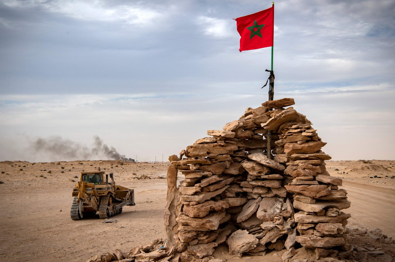 A bulldozer passes by a hilltop manned by Moroccan soldiers on a road between Morocco and Mauritania in Guerguerat located in the Western Sahara, Nov. 23, 2020. (AFP Photo)