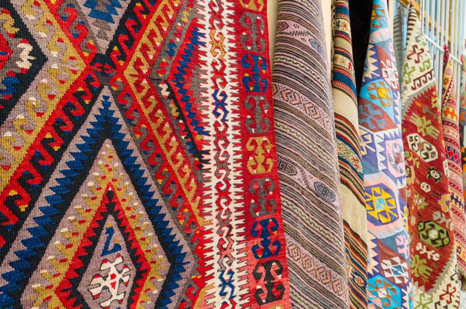 Different traditional Turkish carpets seen hanging on a wall on a street in old town Kaleiçi, Antalya, southern Turkey. (Shutterstock Photo)