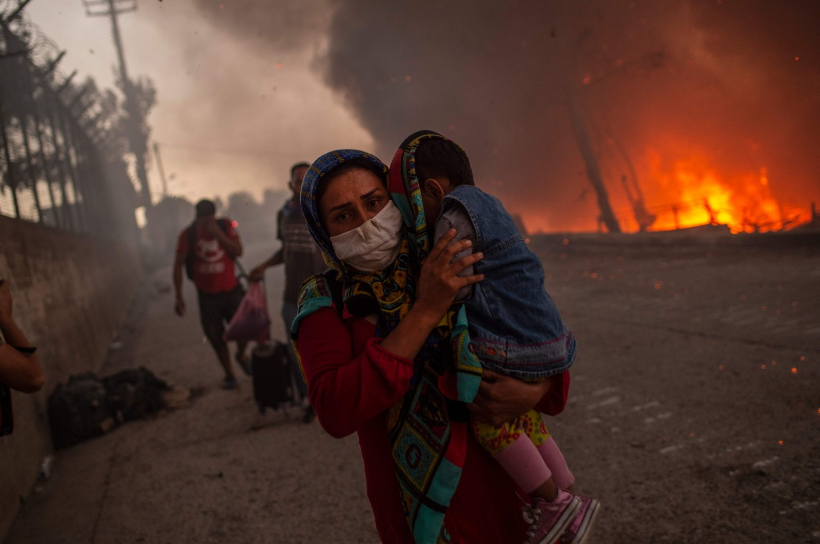 A woman carries a child past flames after a major fire broke out in the Moria migrants camp on the Aegean island of Lesbos, Greece, Sept. 9, 2020. (AFP Photo)
