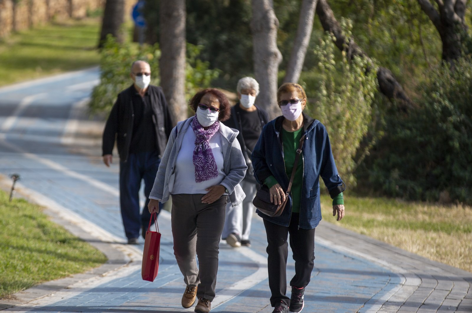 People wearing protective masks walk in a park in Antalya, southern Turkey, Nov. 24, 2020. (AA Photo)