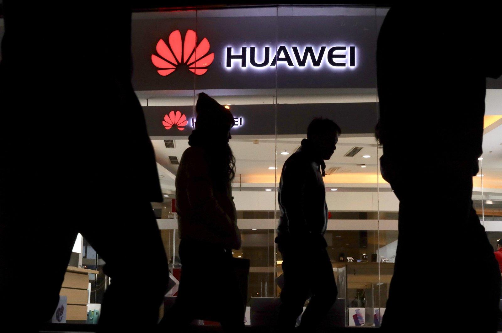 Pedestrians walk past a Huawei retail shop in Beijing, Dec. 6, 2018. (AP Photo)