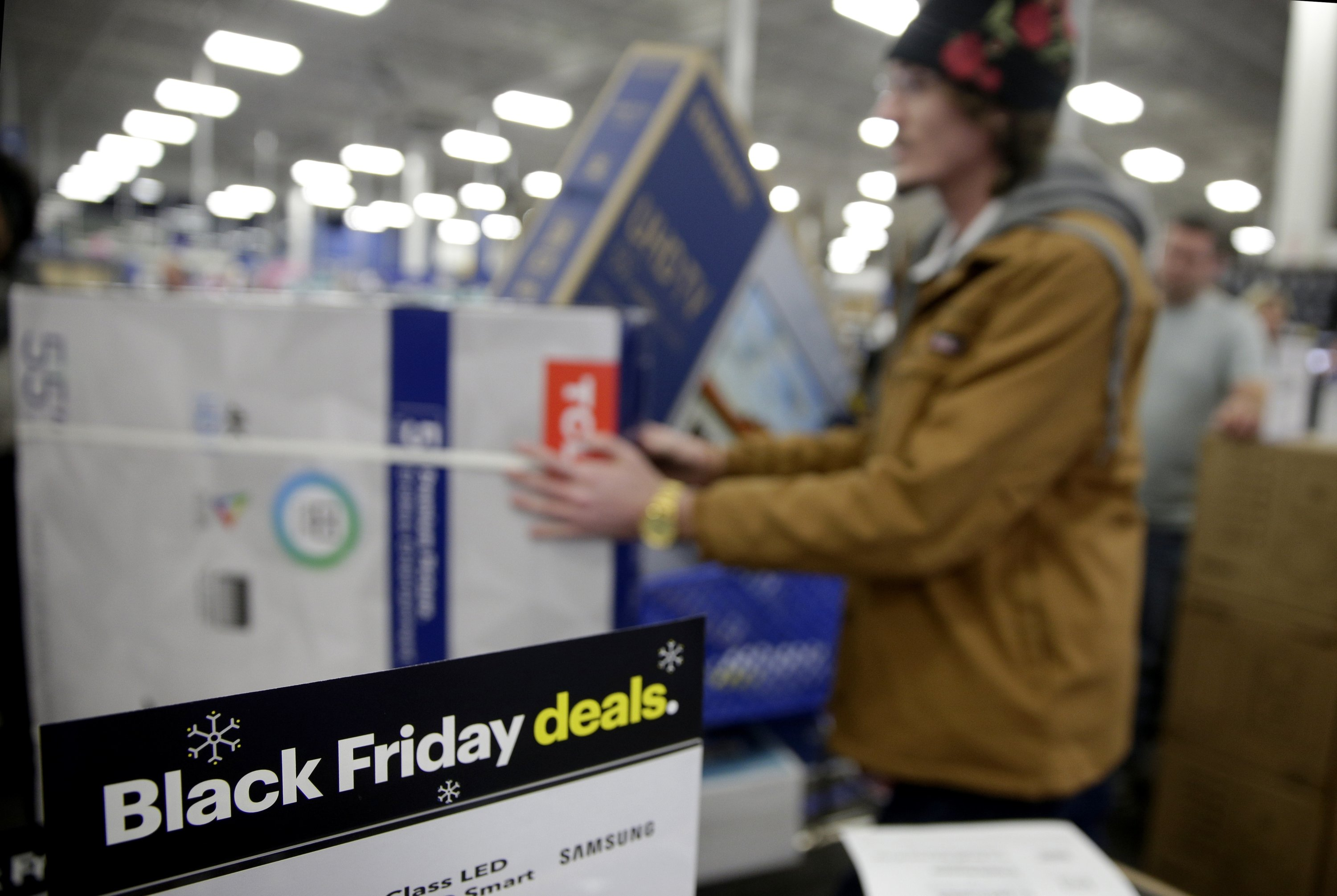 In this Nov. 22, 2018, file photo people wait in line to buy televisions as they shop during an early Black Friday sale at a Best Buy store on Thanksgiving Day in Overland Park, Kan. (AP Photo)