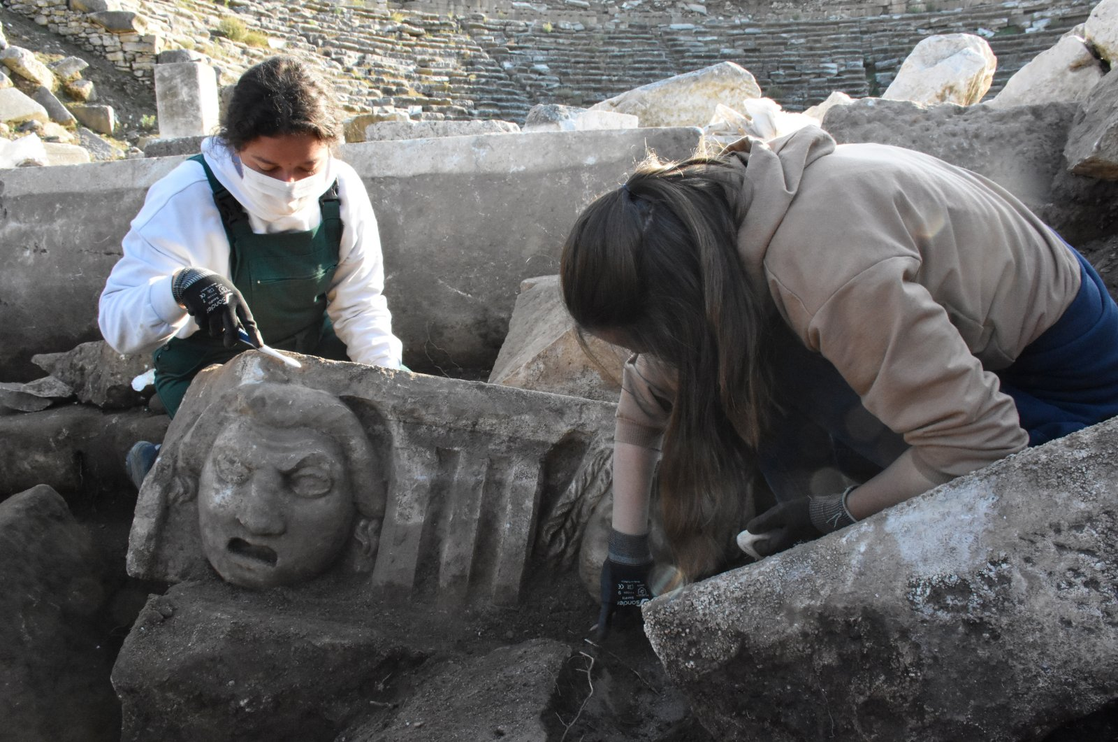 An archaeologist works on a face mask in the ancient city of Stratonikeia, Muğla, southwestern Turkey, Nov. 24, 2020. (AA PHOTO)