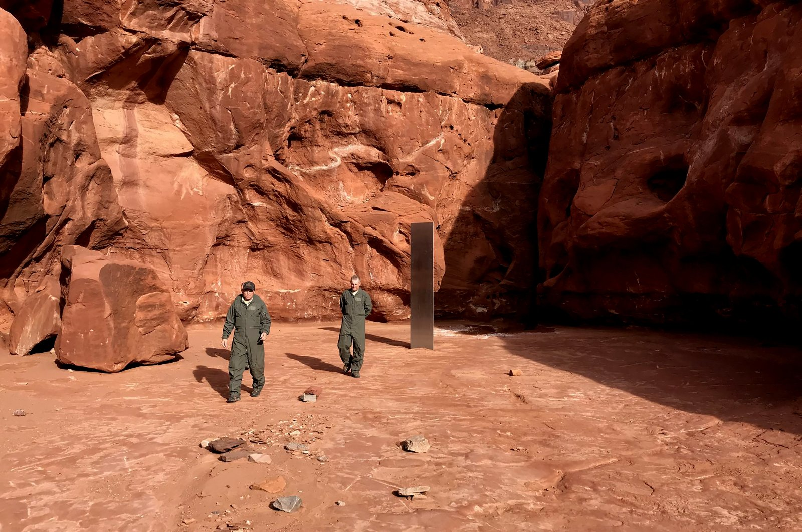 Utah state workers walk near a metal monolith in the ground in a remote area of red rock in the U.S. state of Utah, Nov. 18, 2020. (Utah Department of Public Safety via AP)