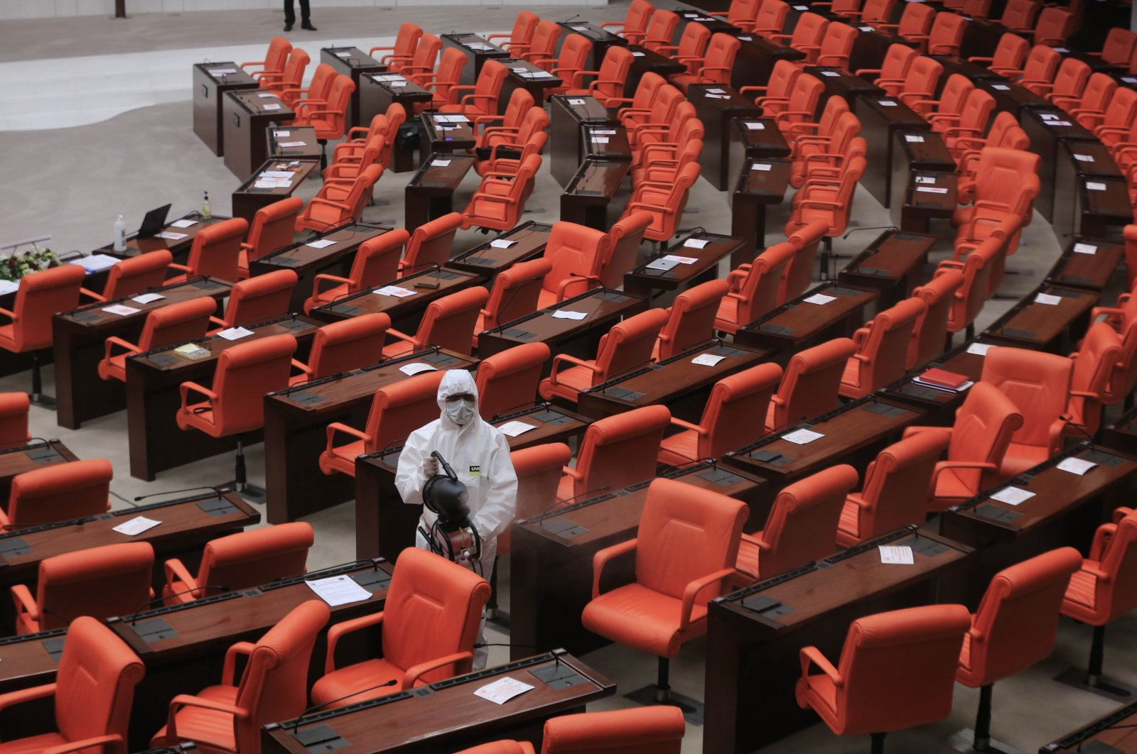 A worker wearing protective gear disinfects the General Assembly of the Turkish Parliament in Ankara, Turkey, Nov. 24, 2020. (AA Photo)