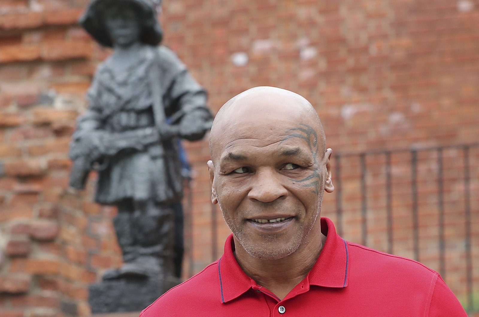 Mike Tyson stands in front of a memorial to Polish suffering during World War II, during a visit to Warsaw, Poland, June 27, 2019. (AP Photo)