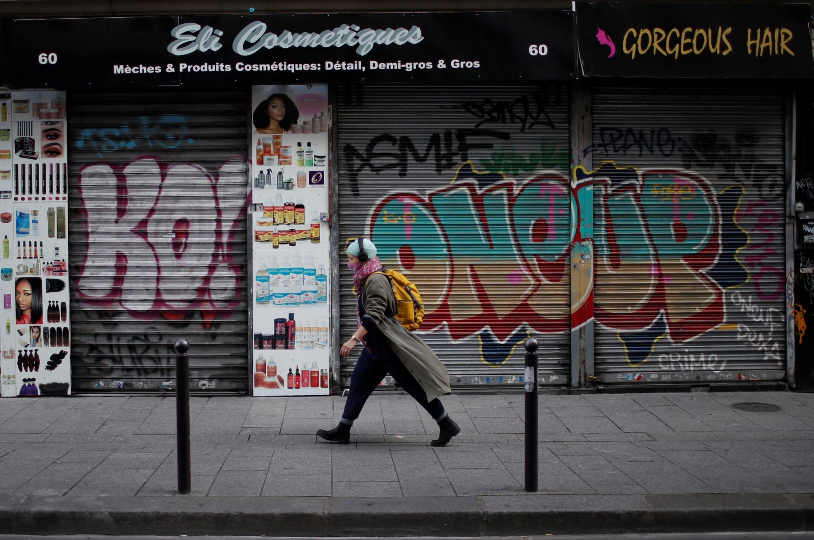A woman, wearing a protective mask, walks past a closed hair and cosmetic shop on a street in Paris during the second national lockdown as the coronavirus outbreak continues in France, Nov. 19, 2020. (Reuters Photo)