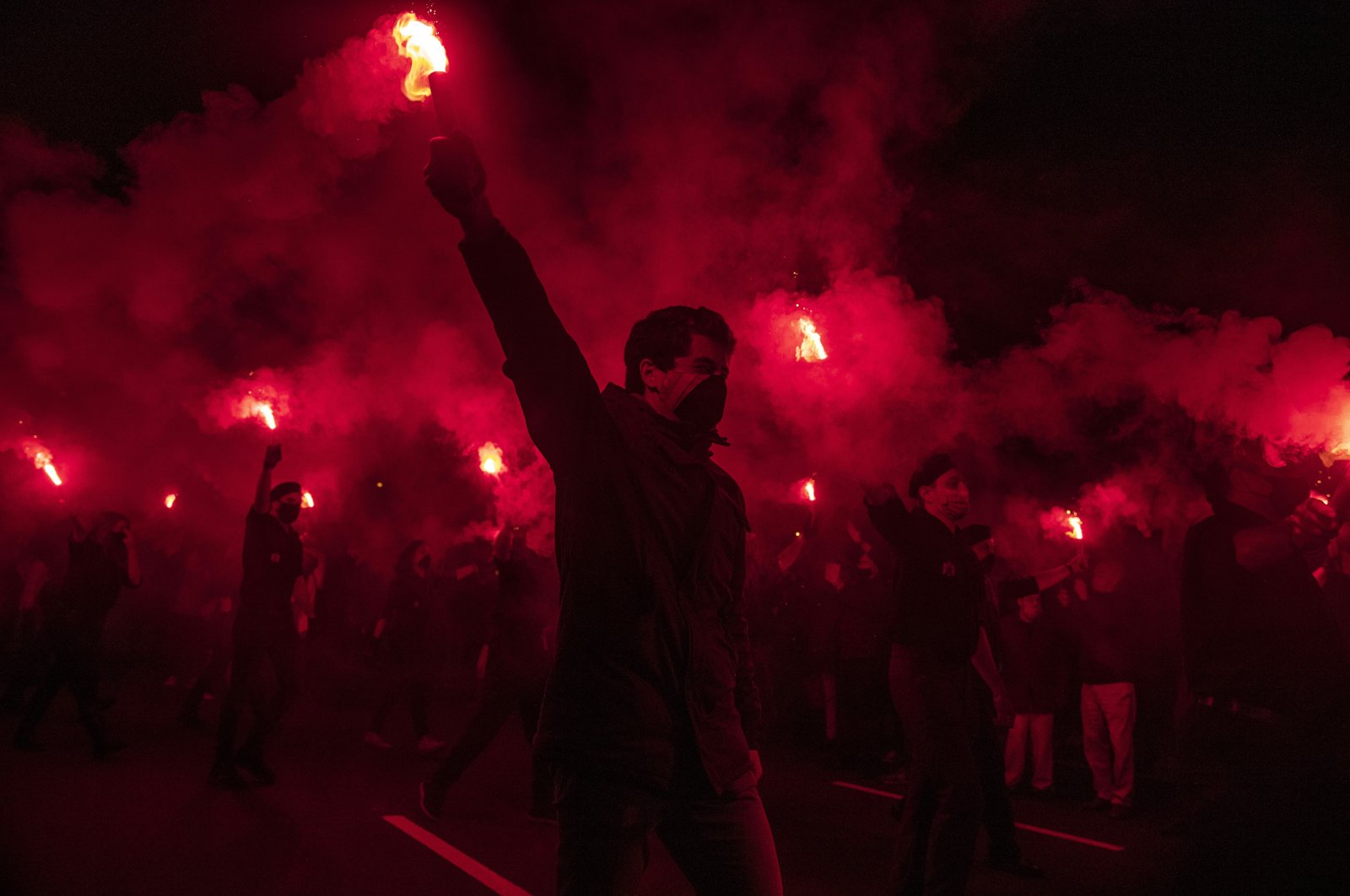 Far-right activists burn flares during a rally marking the anniversary of the death of Jose Antonio Primo de Rivera, founder of the Spanish fascist party, the Falange, in Madrid, Spain, Nov. 20, 2020. (AP Photo)