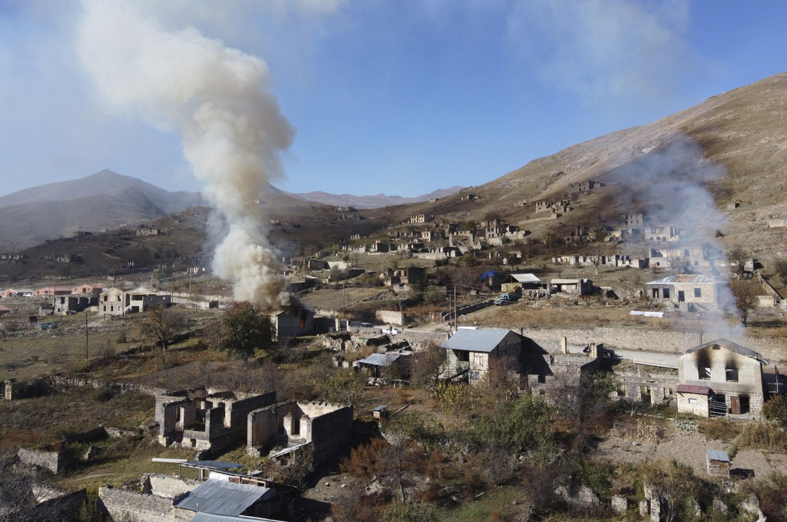 In this photo taken with a drone, smoke rises from burning houses as Armenians leave the occupied region of Nagorno-Karabakh for Armenia,  Nov. 14, 2020. (AP Photo)