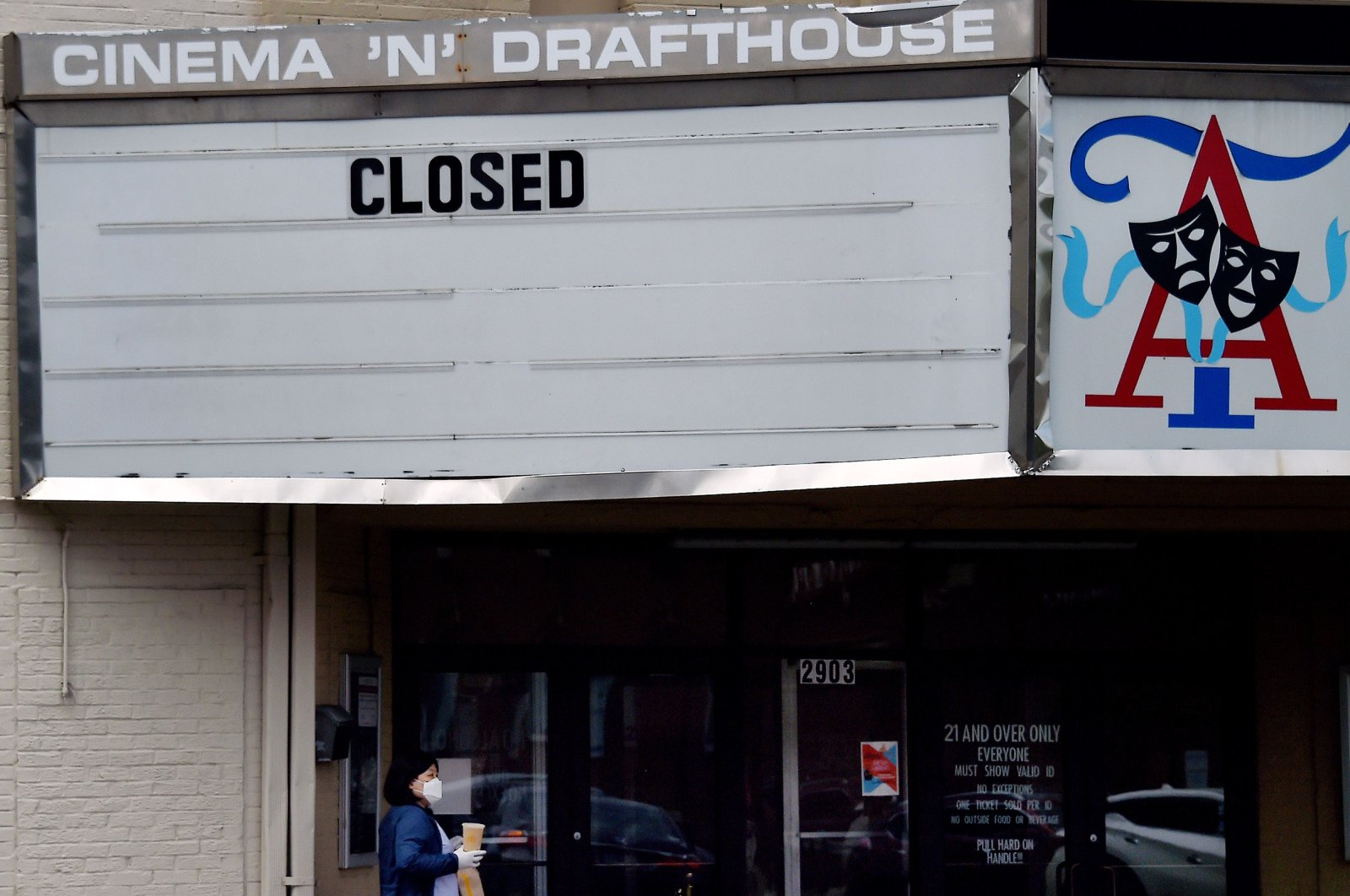 A woman walks past the closed Arlington Cinema and Drafthouse movie theater amid the coronavirus pandemic in Arlington, Virginia, May 13, 2020. (AFP Photo)