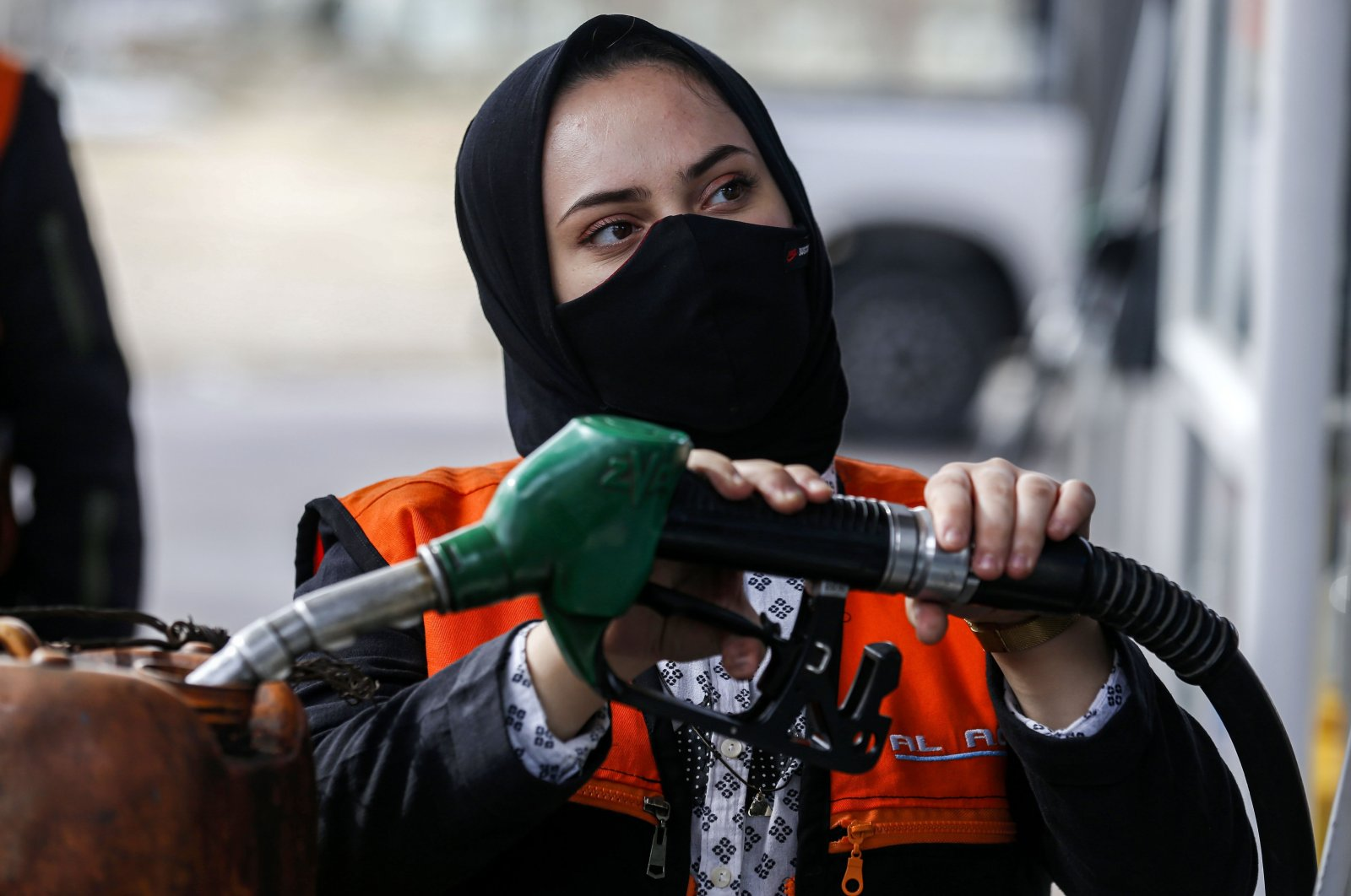 Salma al-Najjar, a 15-year-old Palestinian who works at a gas station to help her family earn income, adds fuel into a jerrycan in Khan Yunis in southern Gaza Strip, Palestine, Nov. 24, 2020. (AFP Photo)