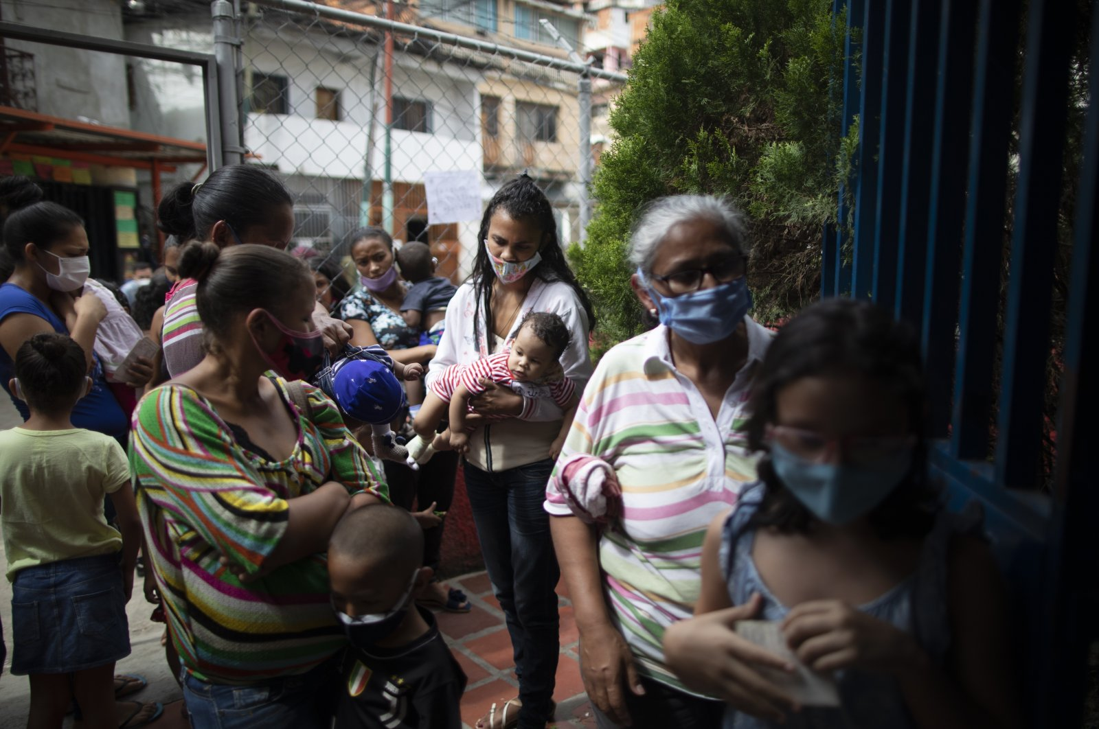 Residents, wearing face masks amid the new coronavirus, wait their turn during a vaccination campaign organized by the Health Ministry, in the El Valle neighborhood of Caracas, Venezuela, Nov. 20, 2020. (AP Photo)