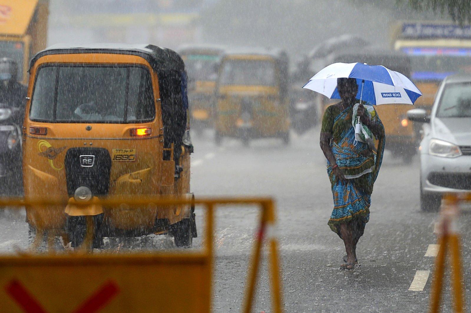A women walks under an umbrella during heavy rains as cyclone Nivar approaches the eastern Indian coast, in Chennai, India, Nov. 24, 2020. (AFP Photo)