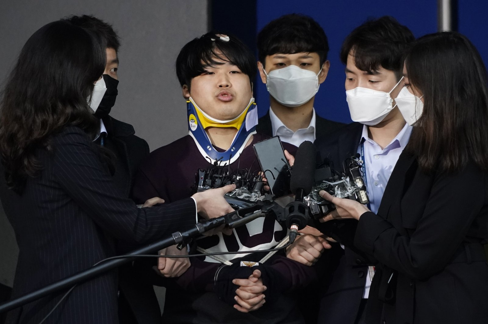 """Cho Ju-bin (C), leader of South Korea's online sexual blackmail ring called the """"Nth room,"""" is surrounded by journalists while walking out of a police station as he is transferred to the prosecutors' office for further investigation in Seoul, South Korea, March 25, 2020. (AP Photo)"""