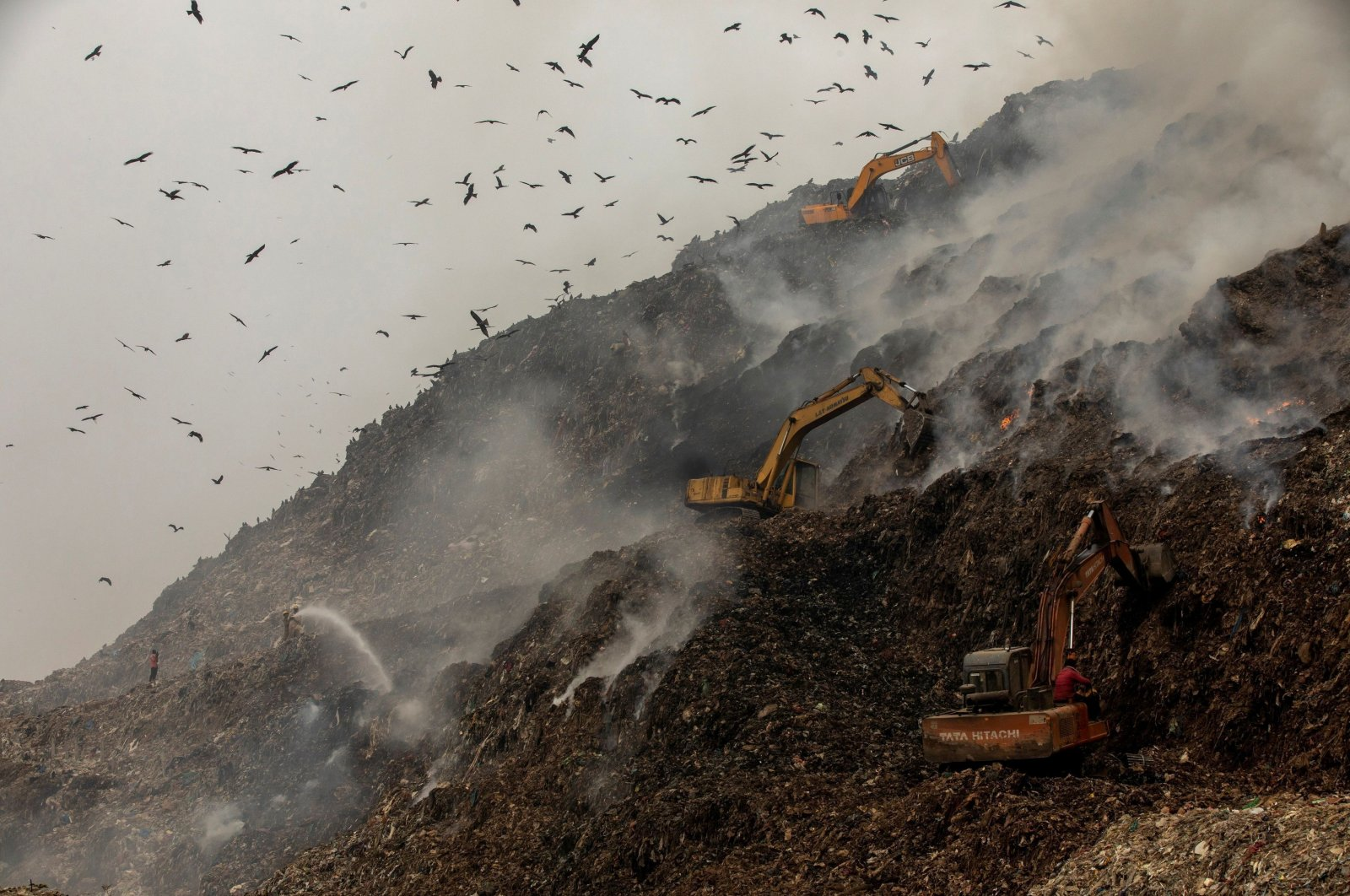 Firefighters and excavators try to douse fire as smoke billows from burning garbage at the Ghazipur landfill site in New Delhi, India, Nov. 25, 2020. (Reuters Photo)