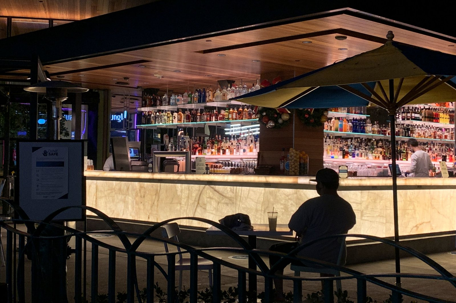 A man sits alone with his drink near the bar as people visit Disneyland where parts of the park opened for more retail and dining as an extension of the Downtown Disney District in Anaheim, California, Nov. 19, 2020. (AFP Photo)