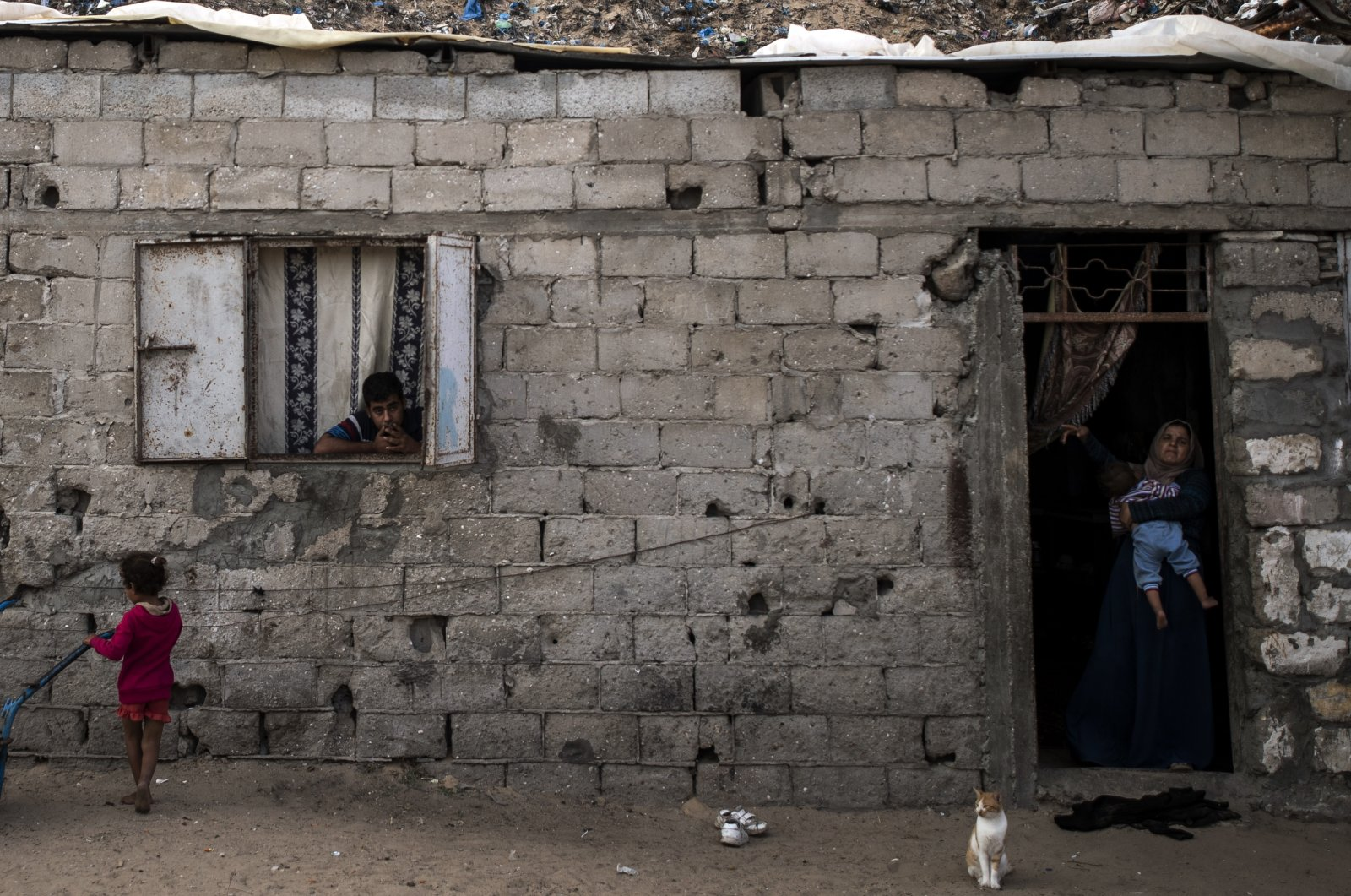 Palestinians are seen looking on from their house in a slum on the outskirts of Khan Younis Refugee Camp, in the southern Gaza Strip, Nov. 25, 2020. (AP Photo)