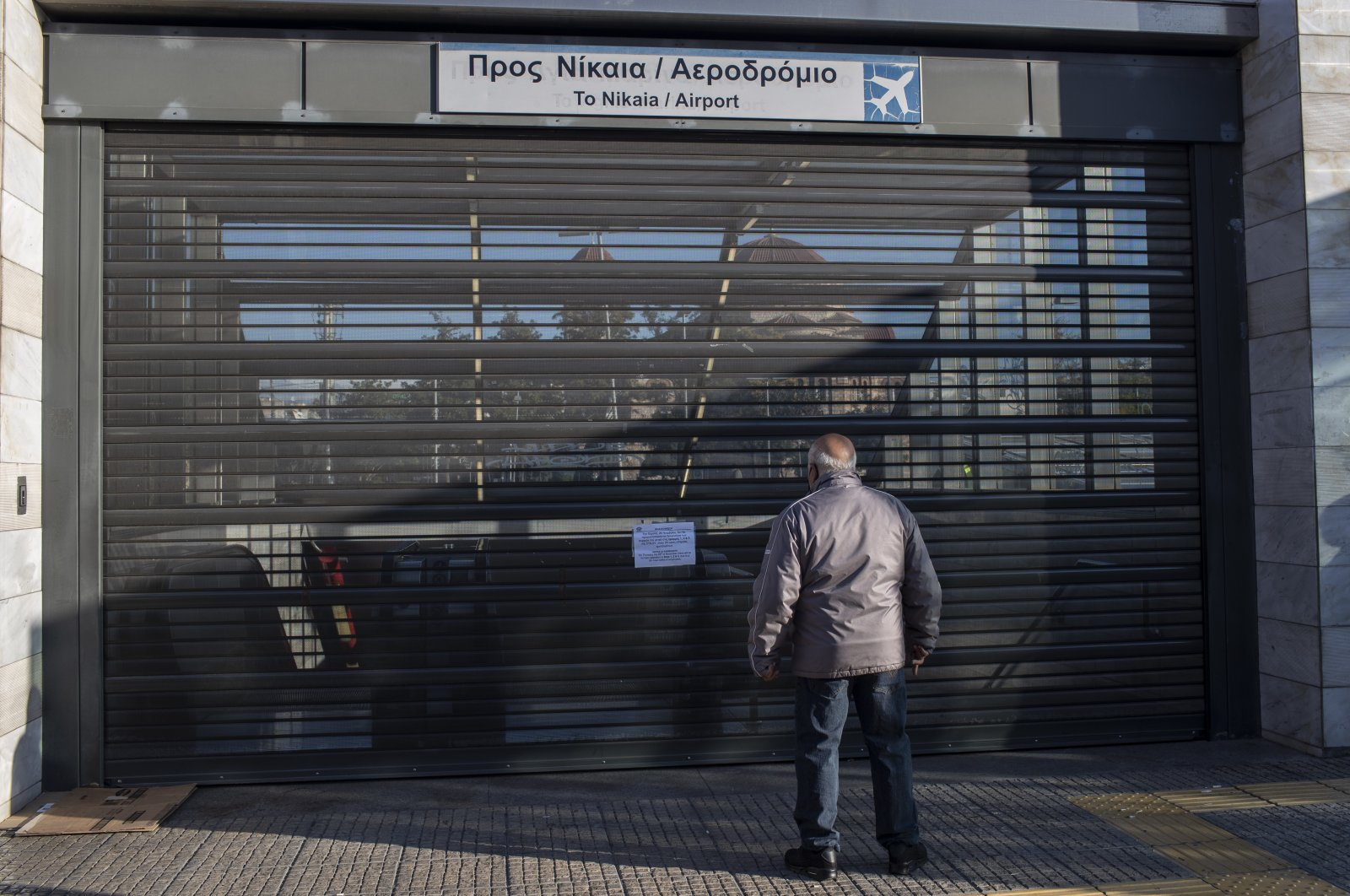 A man looks through the shuttered entrance of a metro station in the Egaleo suburb of Athens during a 24-hour strike, Nov. 26, 2020. (AP Photo)