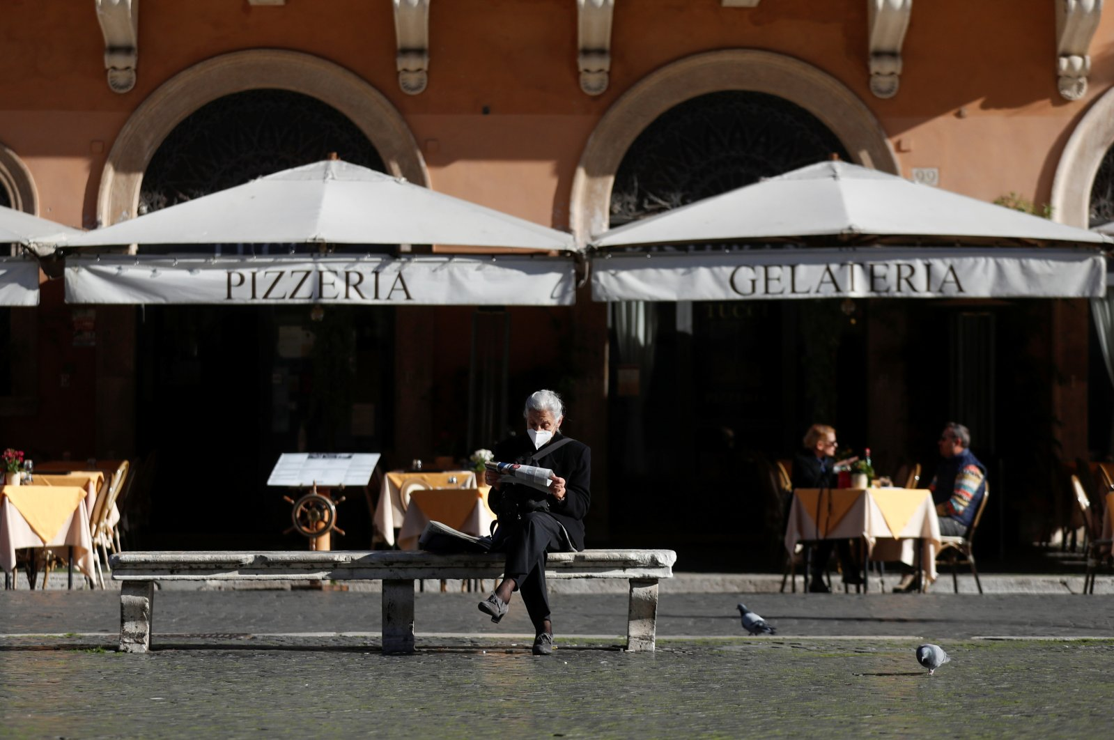 A woman sits on a bench reading a newspaper in Piazza Navona square, Rome, Italy, Nov. 23, 2020. (REUTERS Photo)