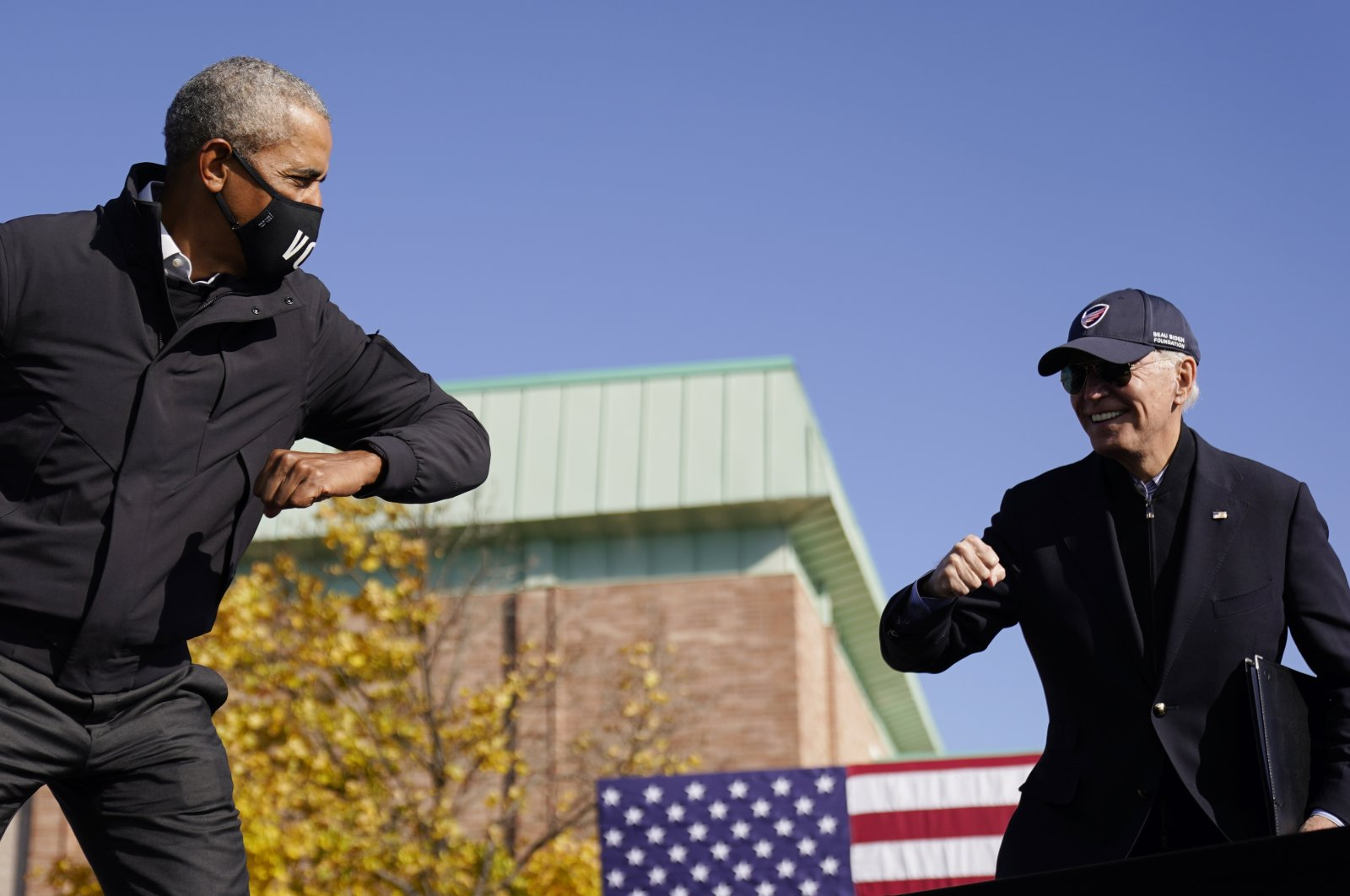 U.S. Democratic presidential candidate Joe Biden and former President Barack Obama greet each other with an air elbow bump at a meeting for the election campaign in Flint, Michigan, U.S., Oct. 31, 2020. (AP Photo)