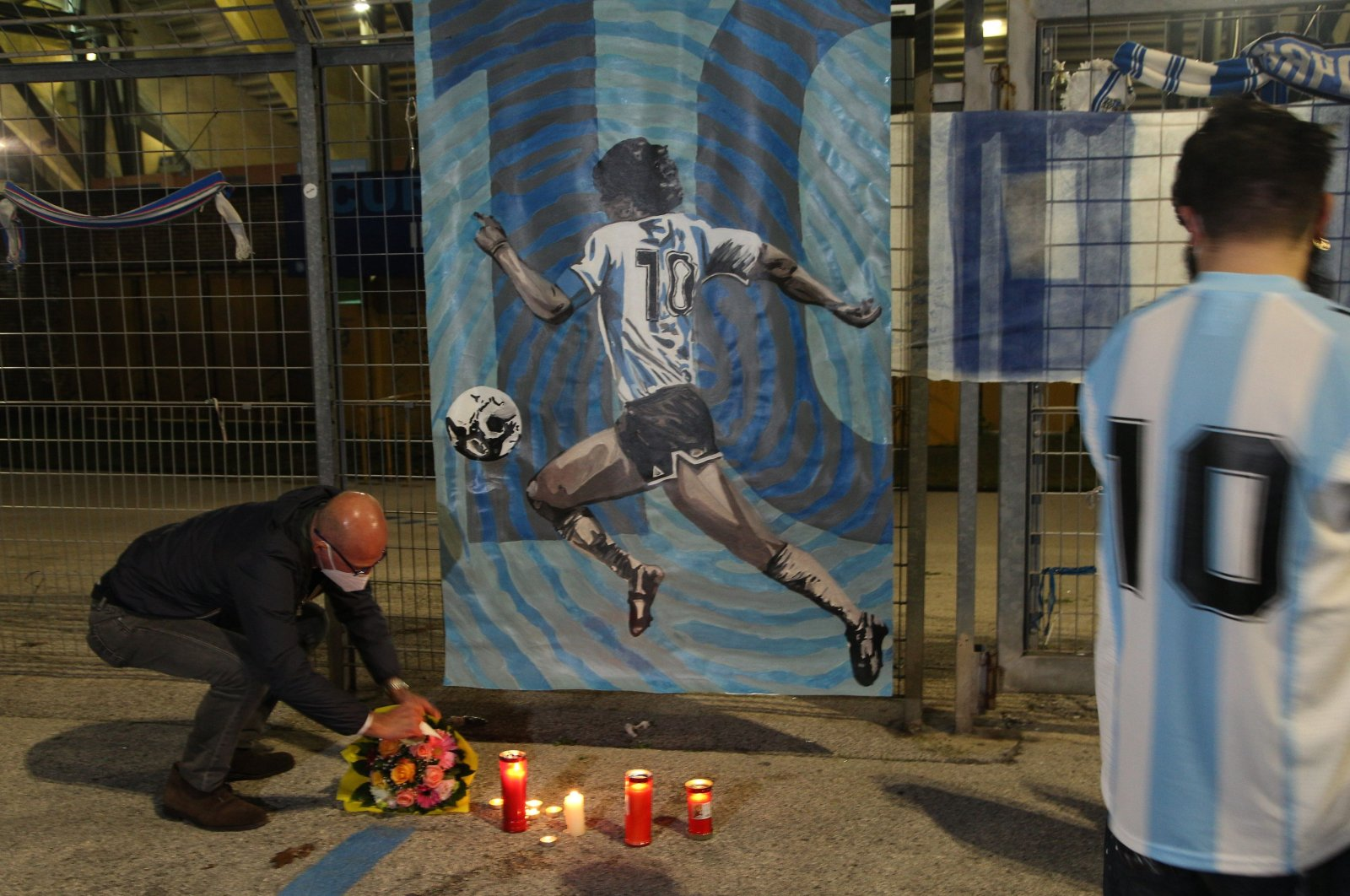 People pay their respects in front of an image of Diego Maradona at the San Paolo, Naples, Italy, Nov. 25, 2020. (AFP Photo)