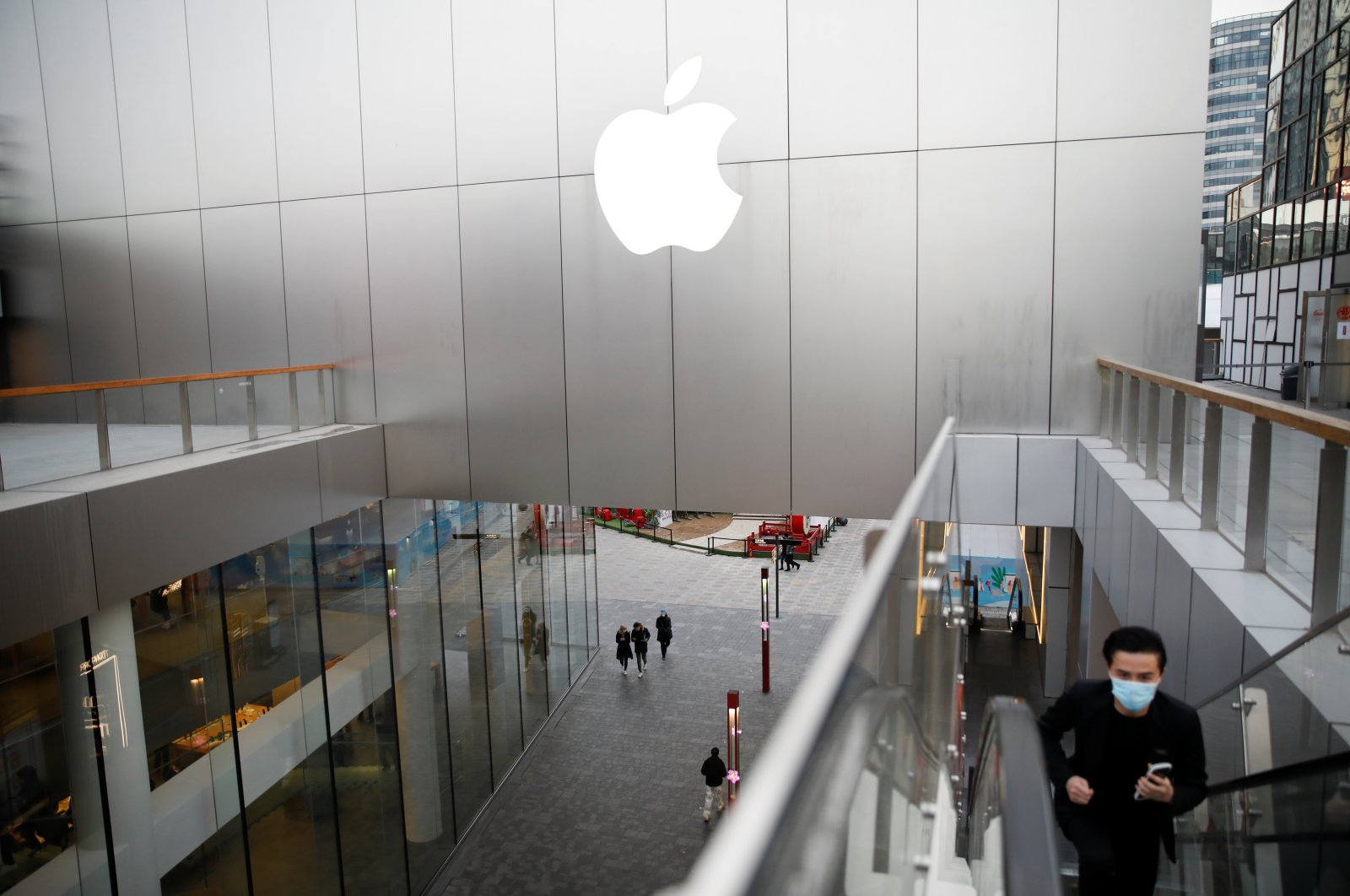 People wearing masks walk past an Apple store at a shopping mall, as the country is hit by an outbreak of the coronavirus, in Beijing, China, Feb. 18, 2020. (Reuters Photo)