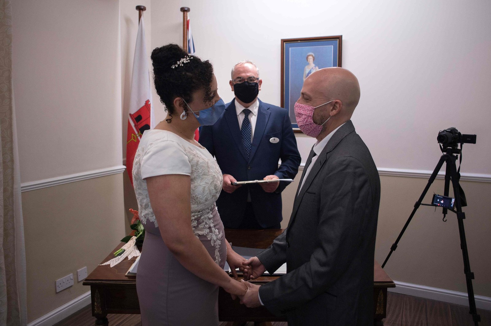 Brazilian Bruno Miani and his Brazilian partner Natalia Senna Alves de Lima (L) get married at the Civil Status and Registration Office in Gibraltar on Nov. 24, 2020. (AFP Photo)