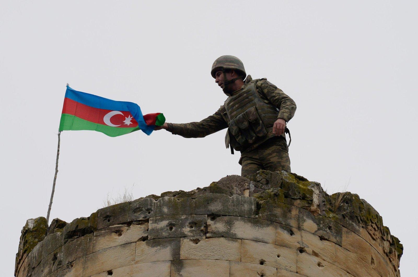 An Azerbaijani soldier attaches a national flag on a tower outside the town of Fuzuli, Azerbaijan, Nov. 26, 2020. (AFP Photo)