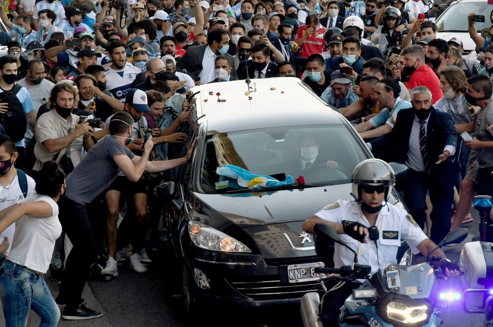 Photo released by Telam showing fans crowding next to the hearse carrying the late Argentine football legend Diego Armando Maradona while leaving Casa Rosada presidential palace to the cemetery, in Buenos Aires, Nov. 26, 2020. (Telam via AFP)