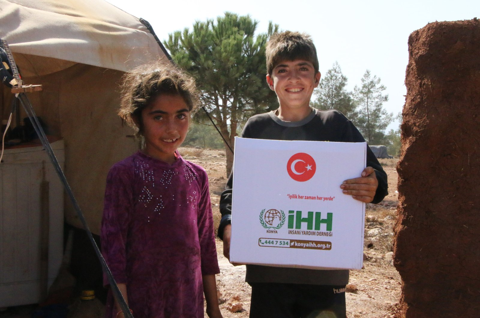 Syrian children pose with a box of aid delivered by Turkey's Humanitarian Relief Foundation (IHH), in this photo provided by the IHH on Nov. 26, 2020. (Photo courtesy of IHH via AA)
