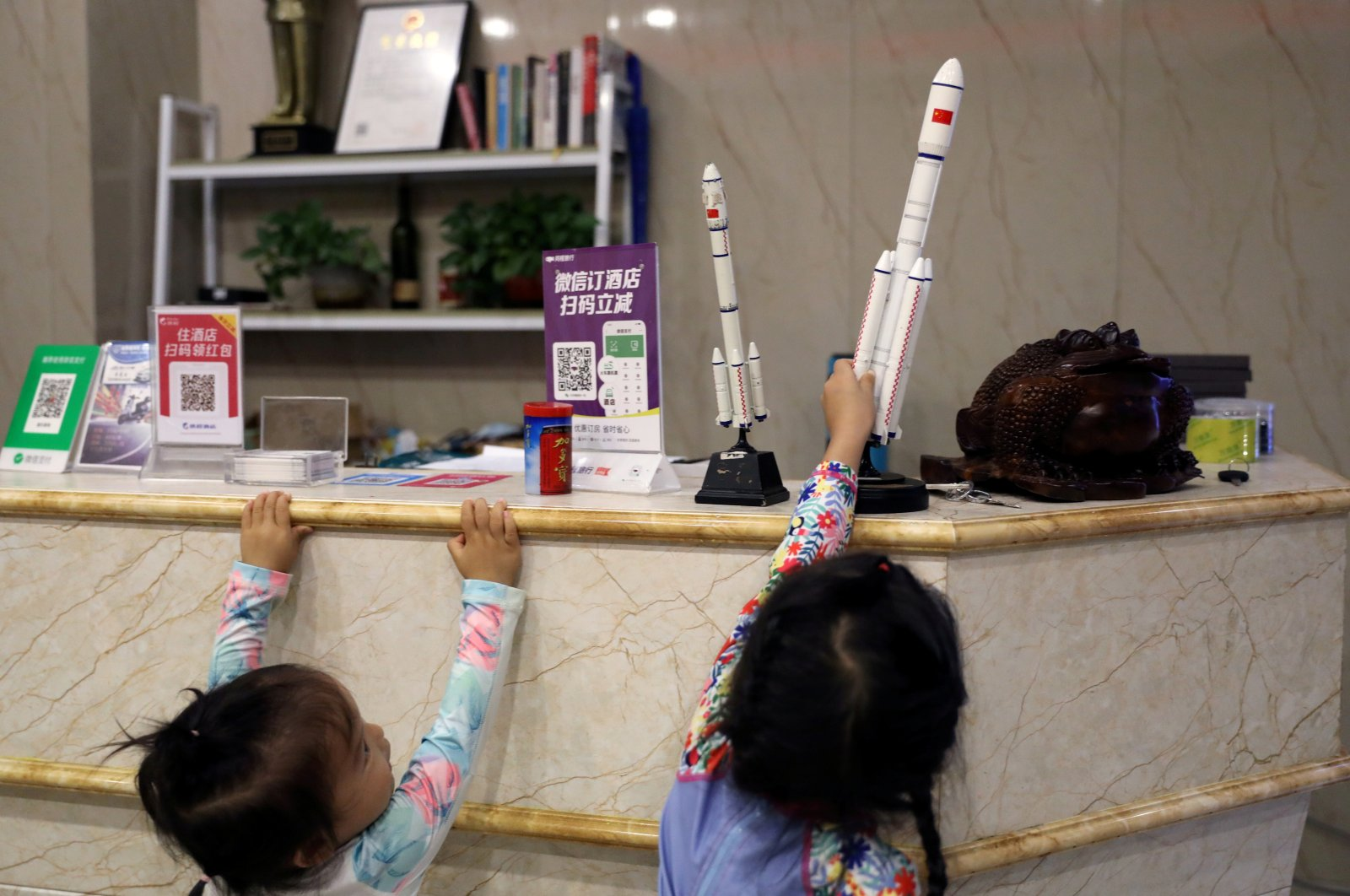 Children play with models of rockets at the reception desk of a hotel in Longlou town, Wenchang, Hainan province, Nov. 22, 2020. (REUTERS Photo)