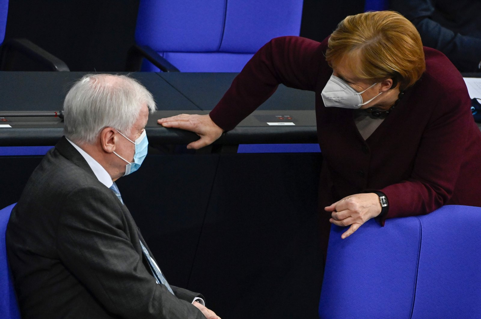 German Chancellor Angela Merkel and German Interior Minister Horst Seehofer wear face masks as they talk during a session at the Bundestag, Berlin, Germany, Nov. 26, 2020. (AFP Photo)