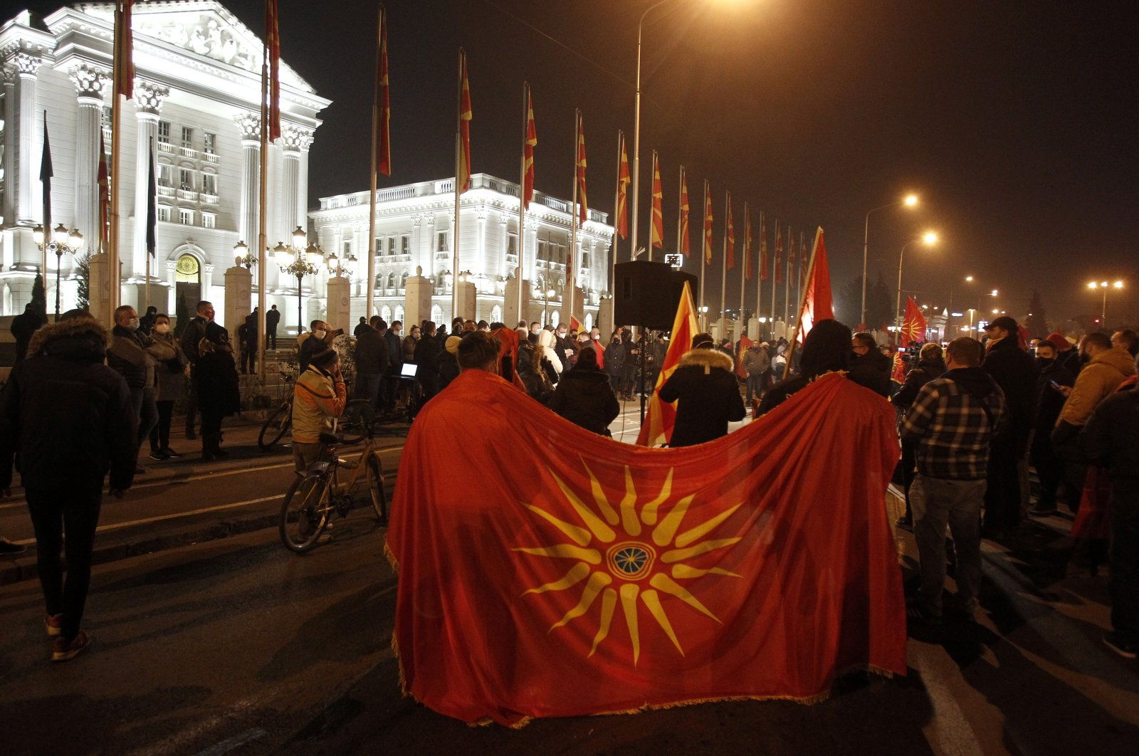 Two men hold an old national flag as opposition supporters gather to protest the government's policy toward Bulgaria, in front of the government building, Skopje, North Macedonia, Nov. 26, 2020. (AP Photo)