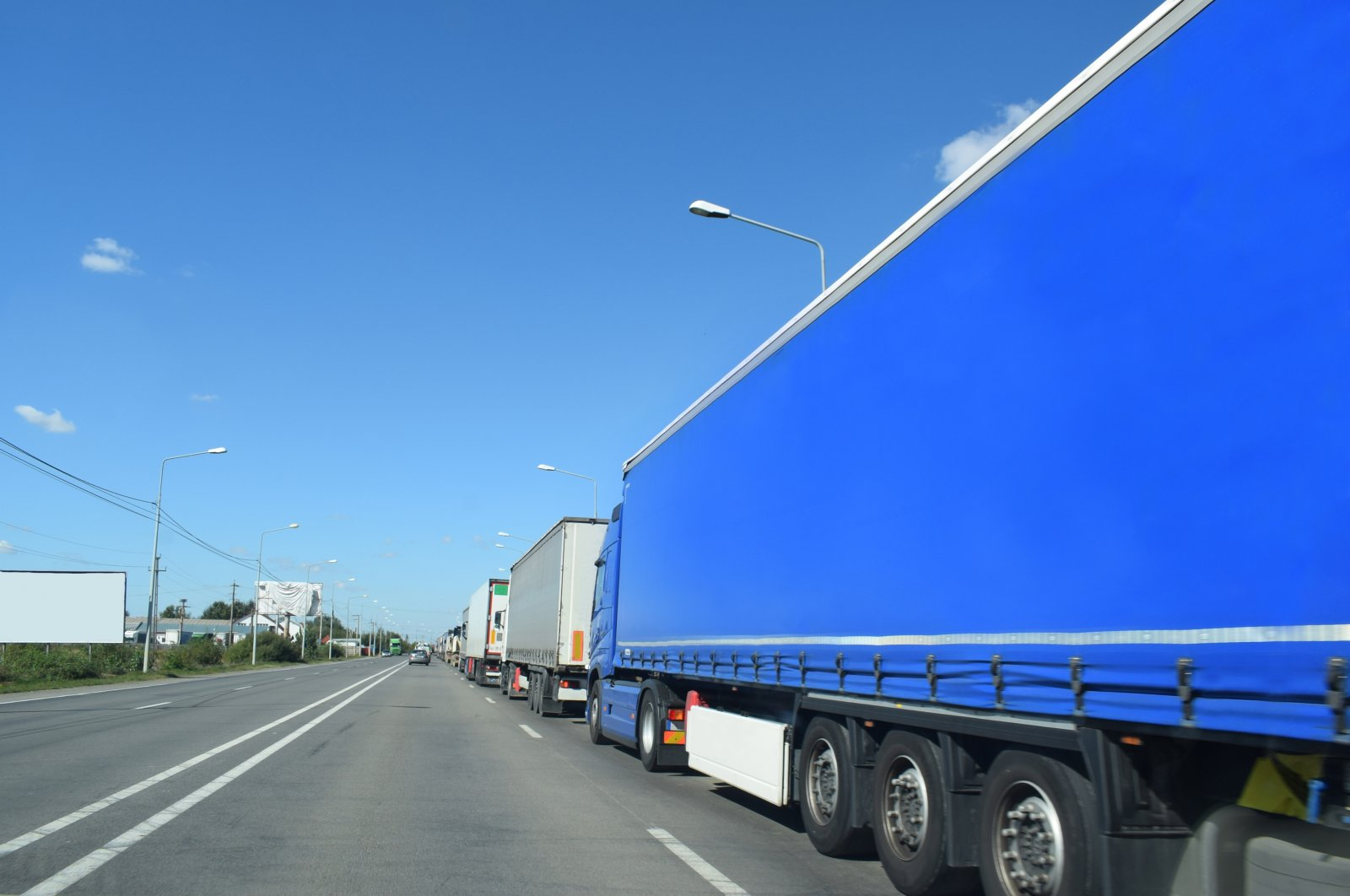 Trucks line up to pass through the border control between Romania and Hungary from the Romanian side. (Shutterstock Photo)