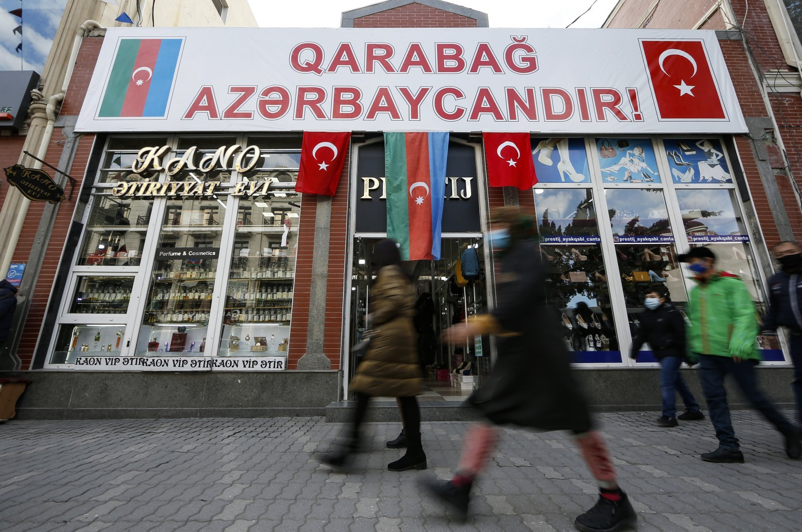 "People walk past a poster reading ""Karabakh is Azerbaijan"" in Ganja, Azerbaijan's second largest city, near the border with Armenia, Nov. 26, 2020. (AP Photo)"
