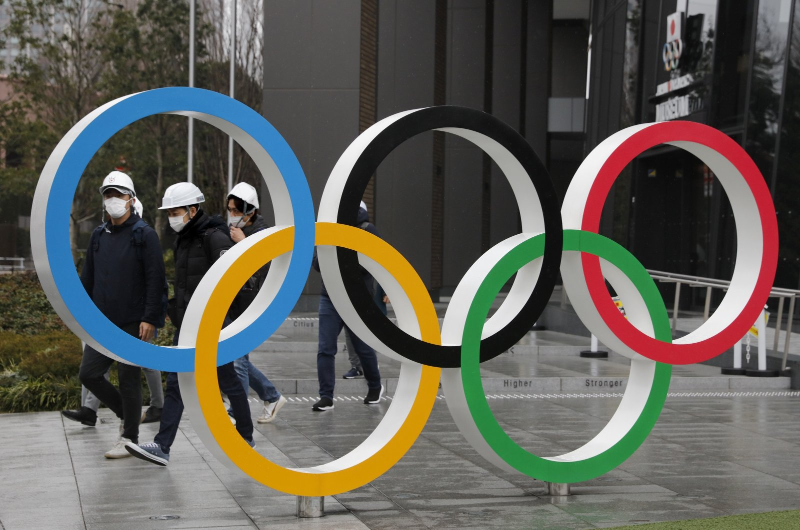 People wearing masks walk past the Olympic rings near the New National Stadium in Tokyo, Japan, March 4, 2020. (AP Photo)