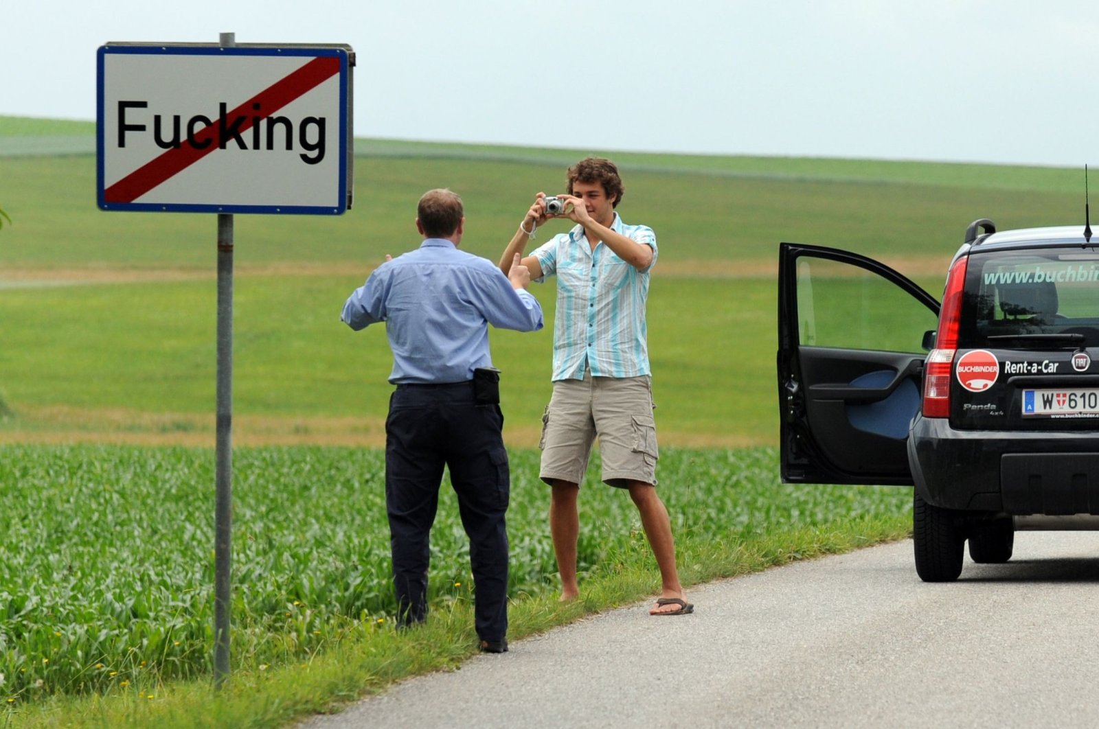 This file photo shows tourists taking pictures of the road sign of the village of Fucking, some 35 kilometers north of Salzburg, Austria, June 18, 2008. (AFP Photo)