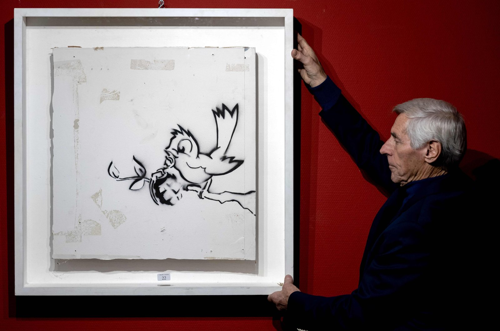 "An employee of the auction house Hessink presents the graffiti painting ""Bird with Grenade,"" made by artist Banksy, in Zwolle, the Netherlands,  Nov. 26, 2020. (AFP PHOTO)"