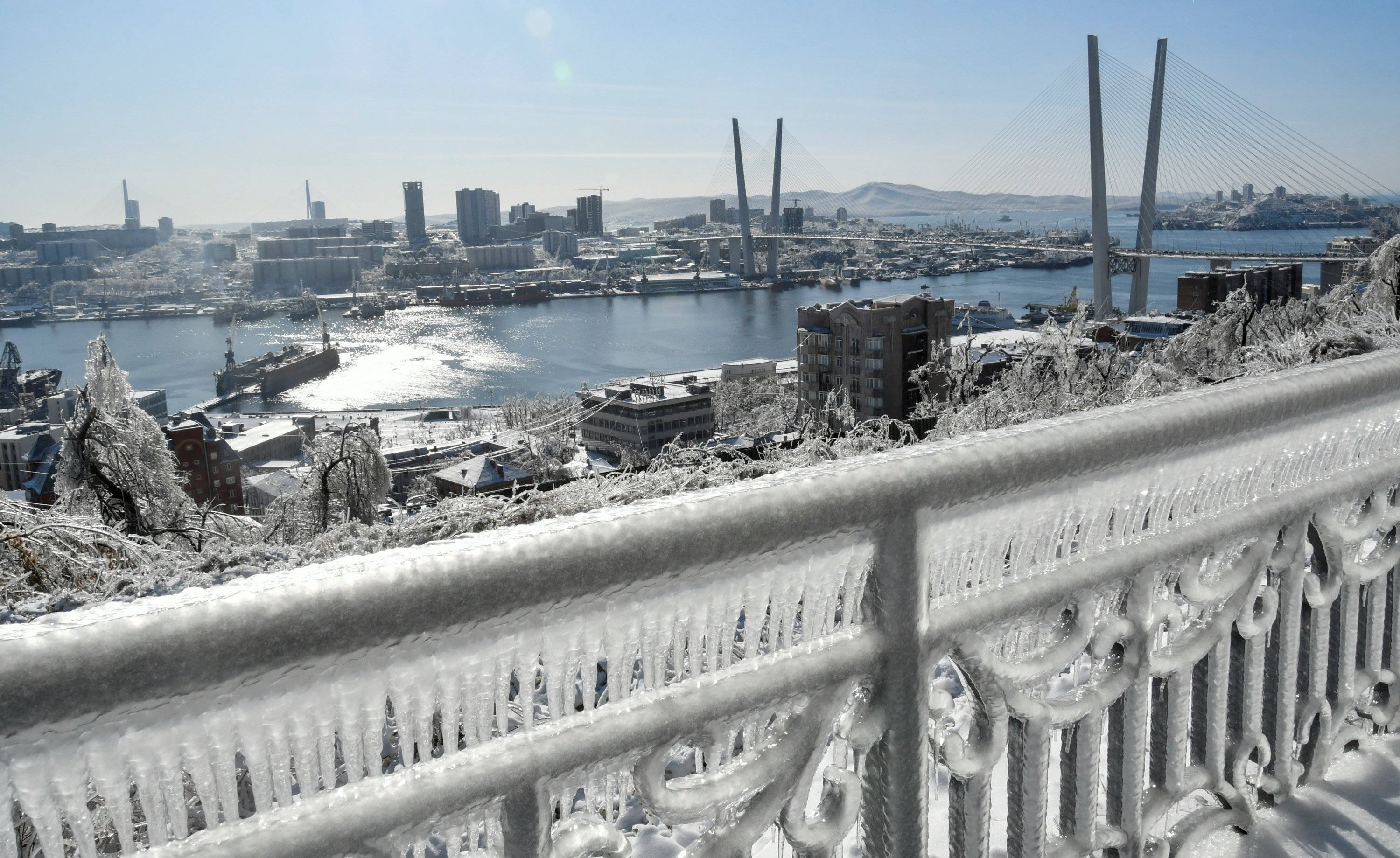 A fence is covered with ice after freezing rain, as a bridge over the Golden Horn bay is seen in the background, in Vladivostok, Russia, Nov. 21, 2020. (Reuters Photo)
