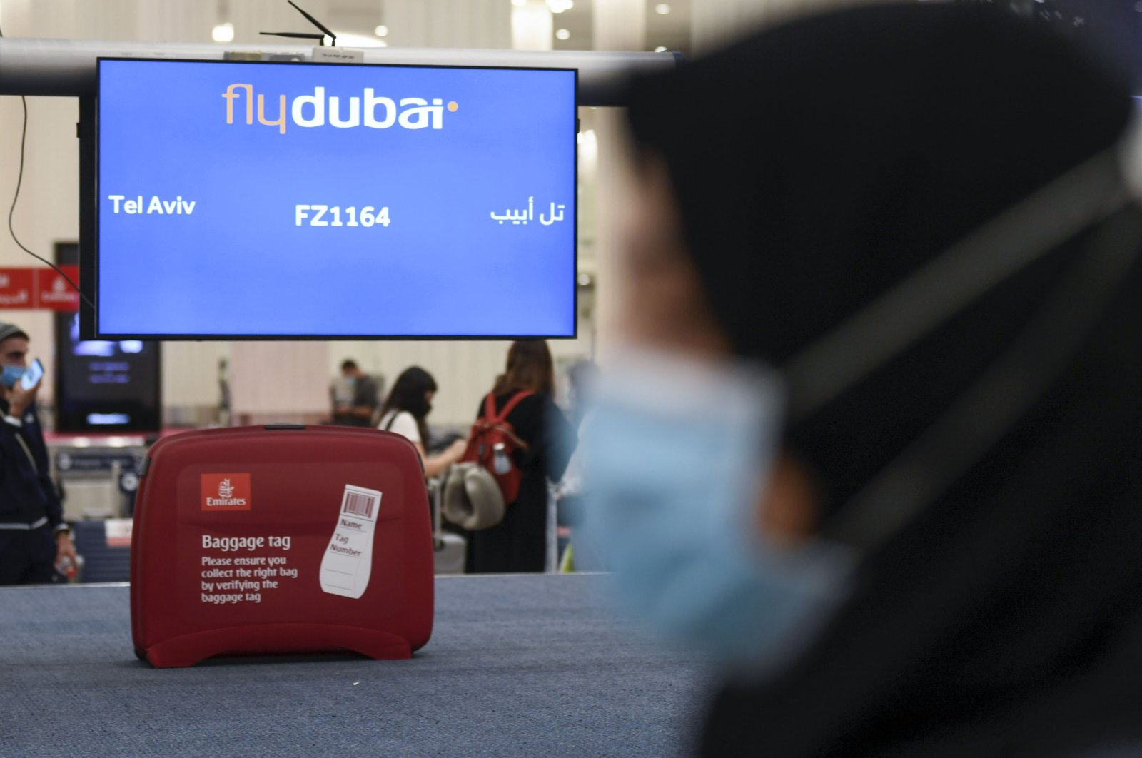 A woman walks past luggage pick-up for arrivals from Tel Aviv to the Dubai airport in the United Arab Emirates, on November 26, 2020, on the first scheduled commercial flight operated by budget airline flydubai, following the normalisation of ties between the UAE and Israel. (AFP Photo)