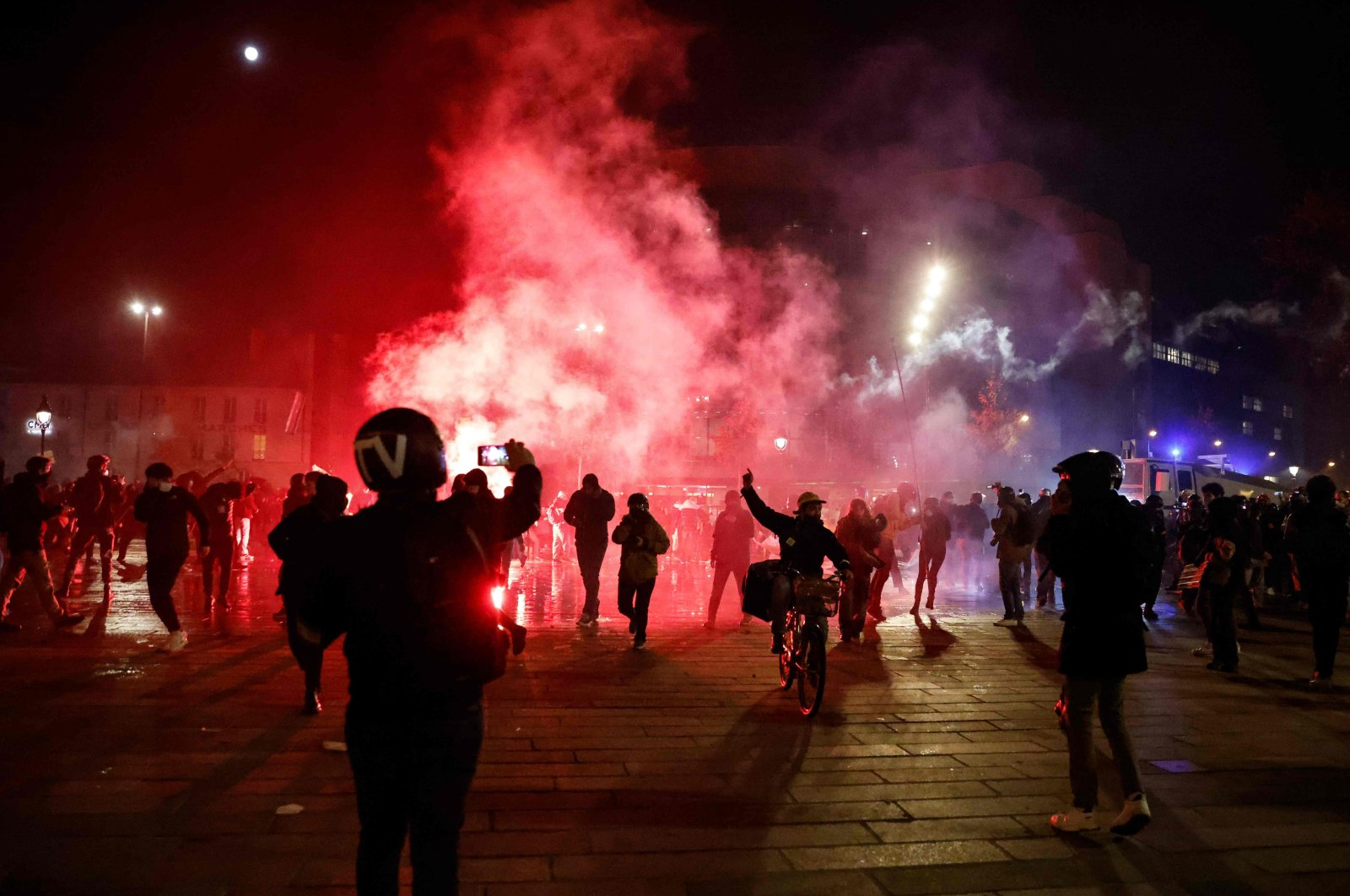 """A TV crew member (L) films with his smartphone as red smoke rise over demonstrators gathered on Place de la Bastille, Paris, Nov. 28, 2020, during a protest against the """"global security"""" draft law, which Article 24 would criminalize the publication of images of on-duty police officers with the intent of harming their """"physical or psychological integrity."""" (AFP Photo)"""