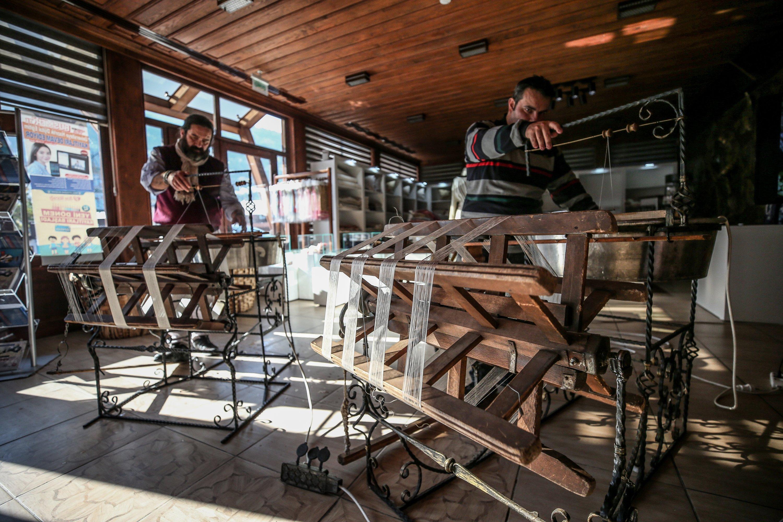 Two men spin silk at the Umurbey Silk Production and Design Center in Bursa, northwestern Turkey, Nov. 27, 2020. (AA PHOTO)