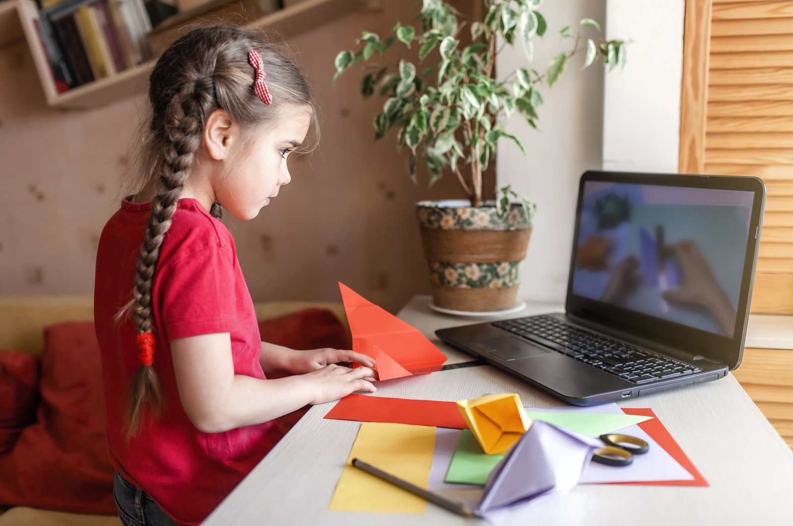 A young student uses colorful paper to create origami fish during an online workshop for distance learning. (iStock Photo)
