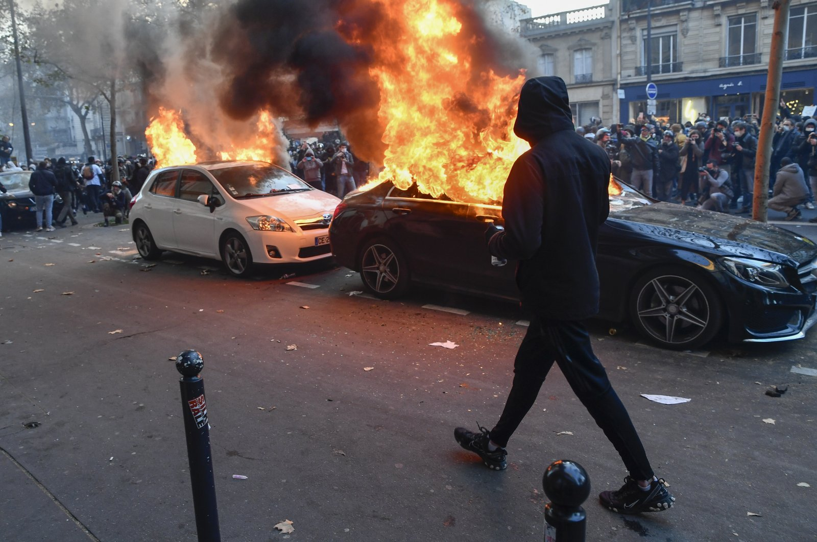 A protester takes a walk past burning cars in Paris on Nov. 29, 2020. (AA Photo)