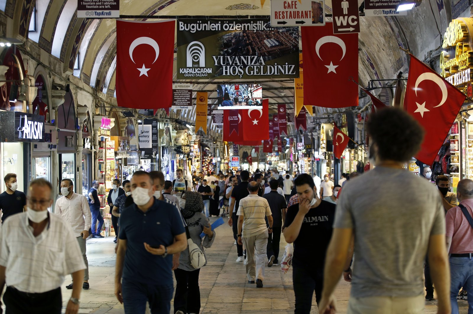 People wearing protective face masks against the spread of the coronavirus walk inside the Grand Bazaar, an iconic 15th-century marketplace, in Istanbul, Aug. 7, 2020. (AP Photo)
