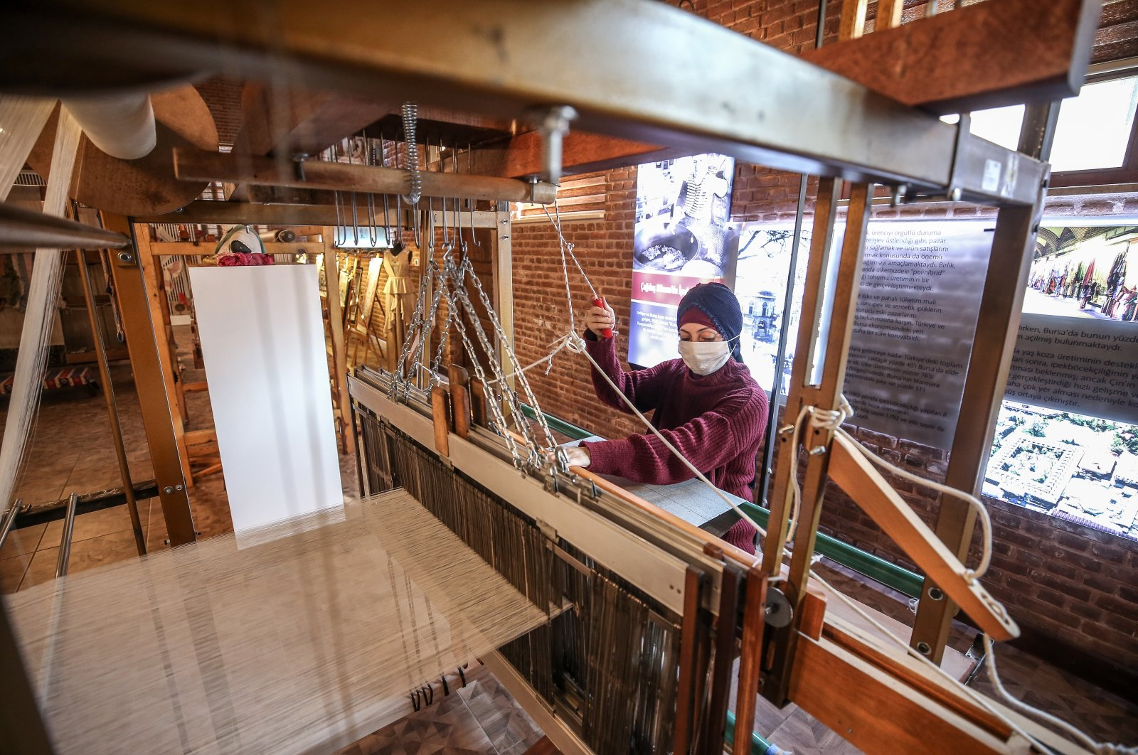 A weaver weaves fabric on the dobby jacquard loom at the Umurbey Silk Production and Design Center in Bursa, northwestern Turkey, Nov. 27, 2020. (AA PHOTO)