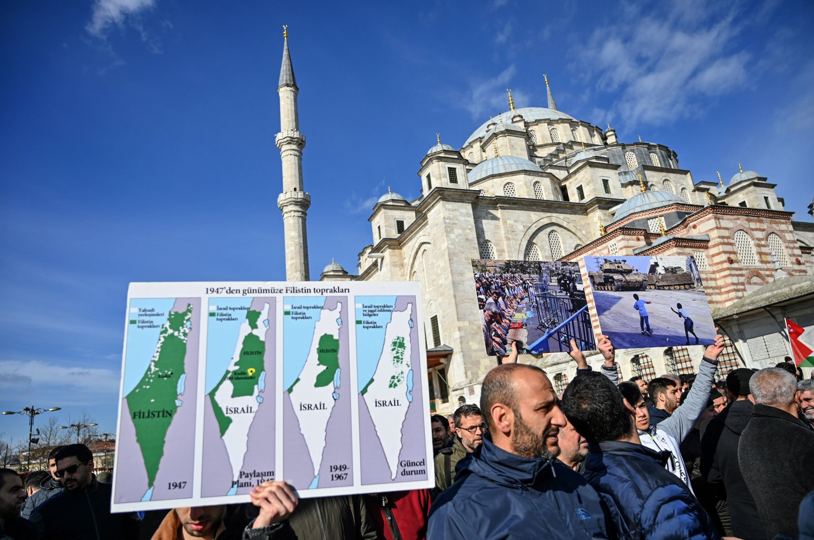 A protester holds a chronological Palestine map during a demonstration at Fatih mosque in Istanbul to protest against the U.S. peace plan, Jan. 31, 2020. (AFP Photo)